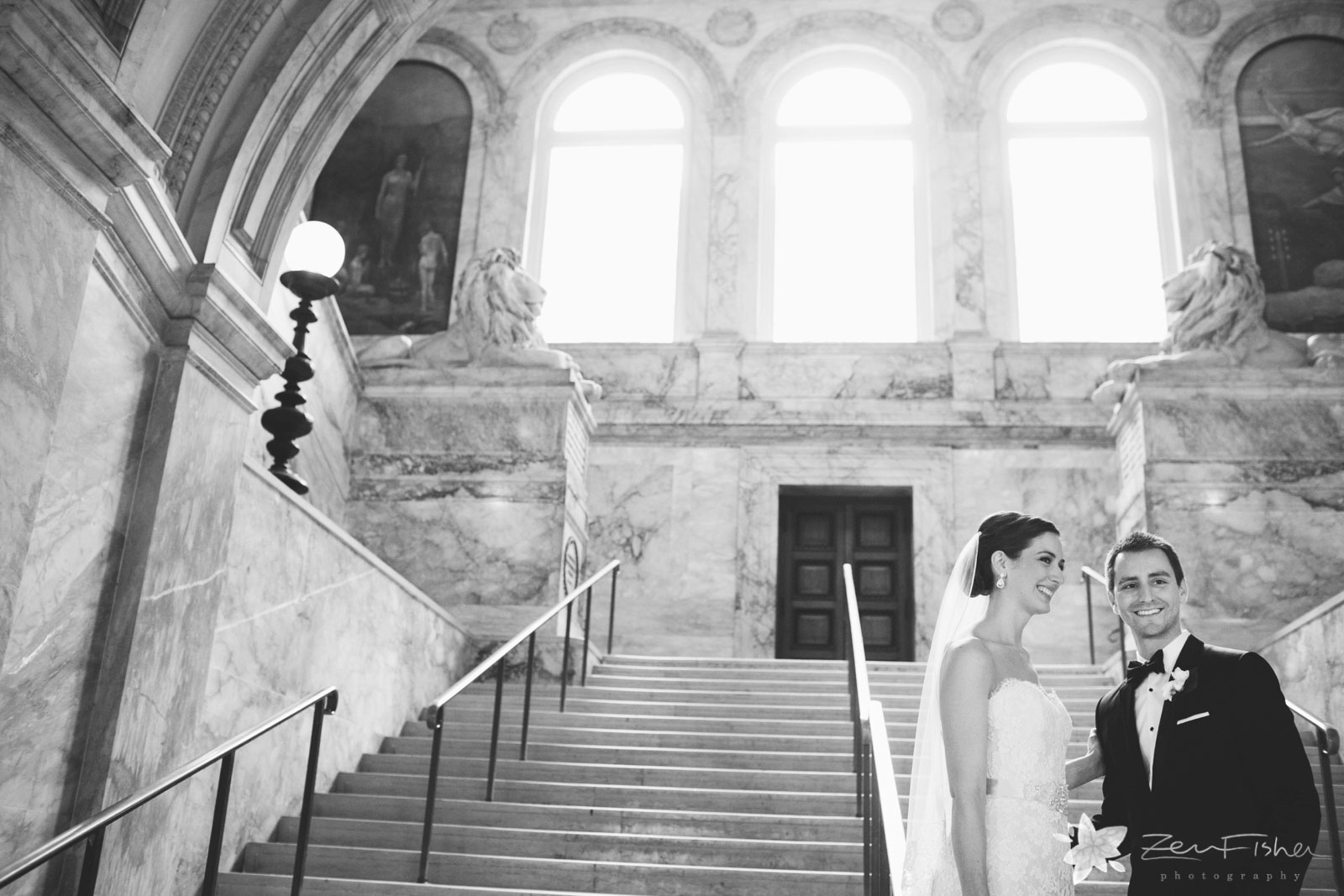 Bride and groom on the marble stairs, smiling and looking away, large windows cast natural light.