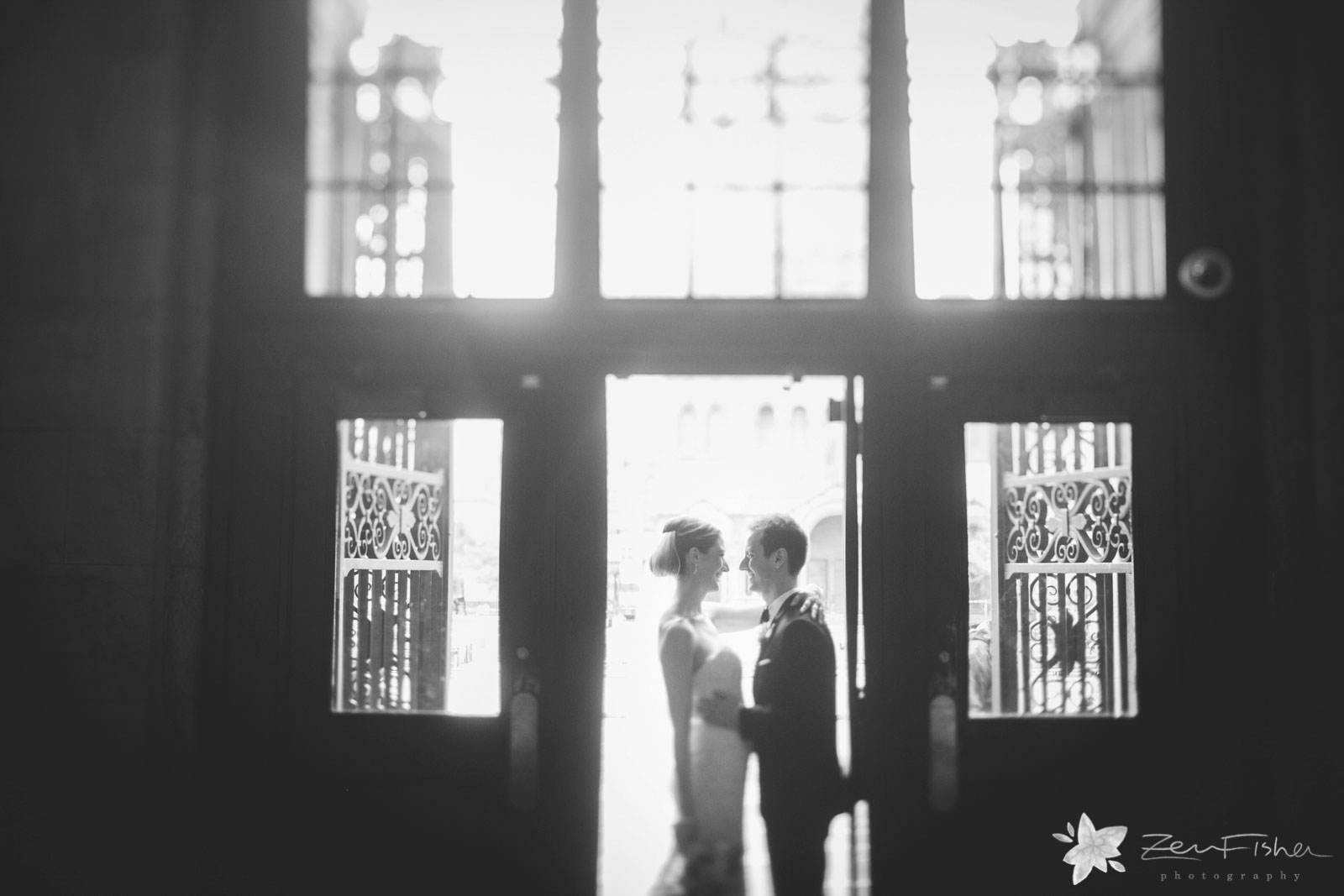 Silhouette of bride and groom holding each other, smiling and looking at each other in doorway.