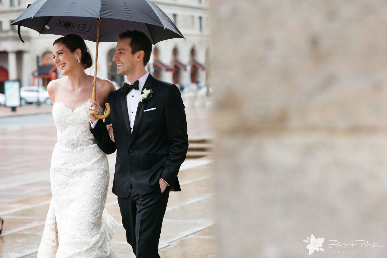 Peeking around the corner at bride and groom walking together under umbrella, smiling.