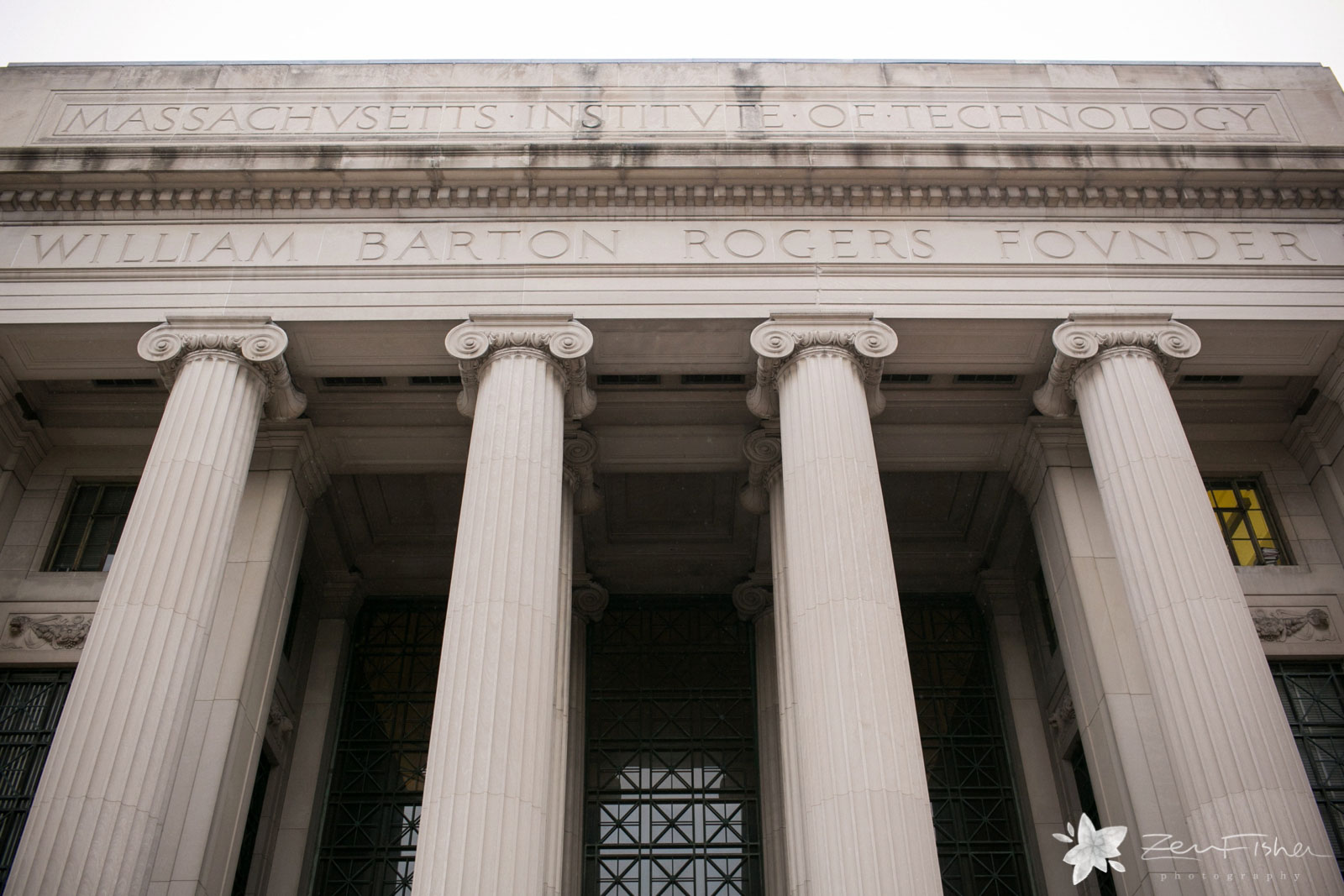 Looking up at the facade of building at MIT with large Roman columns.