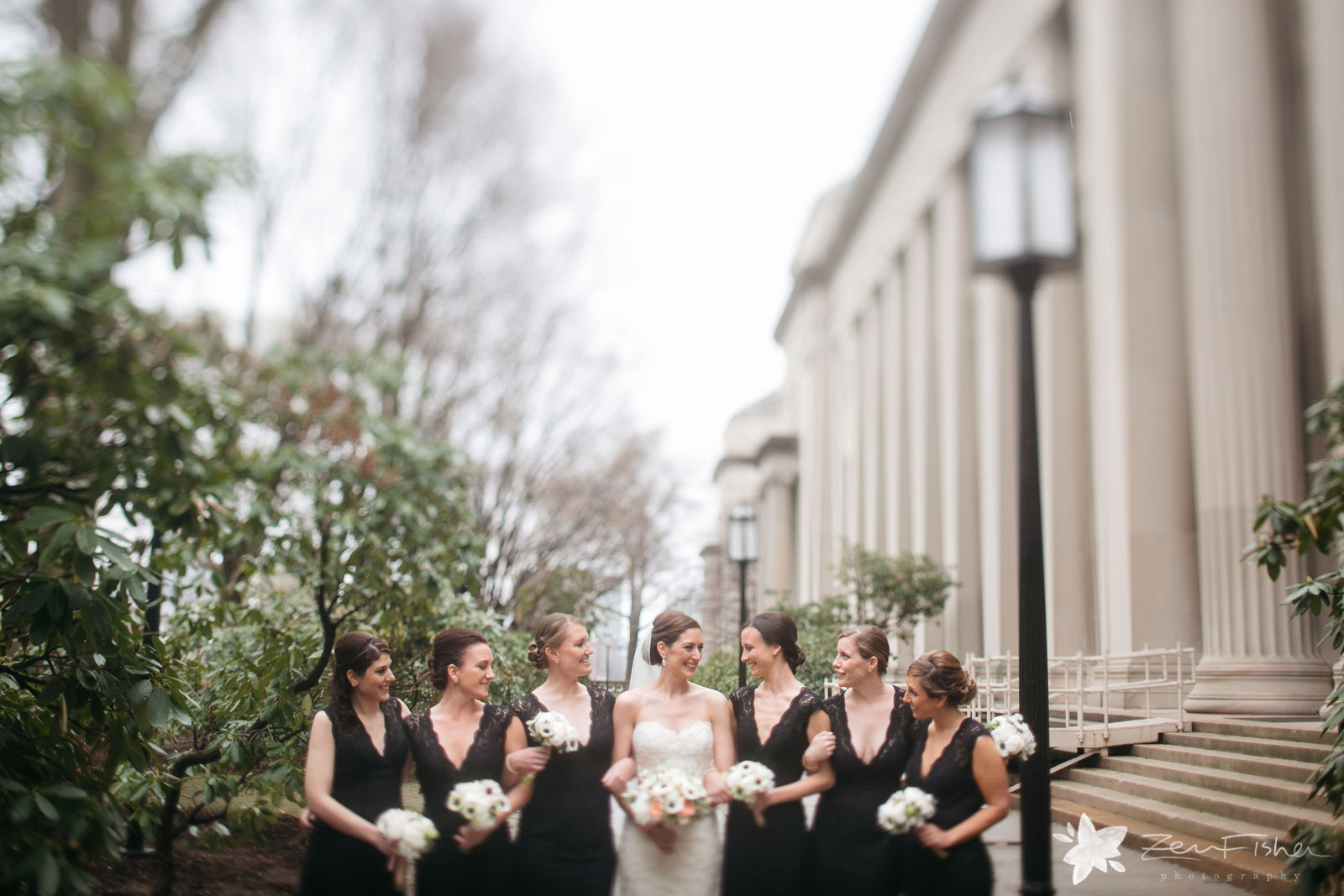 Bride and bridal party portrait looking at each other, smiling in garden with architectural columns.