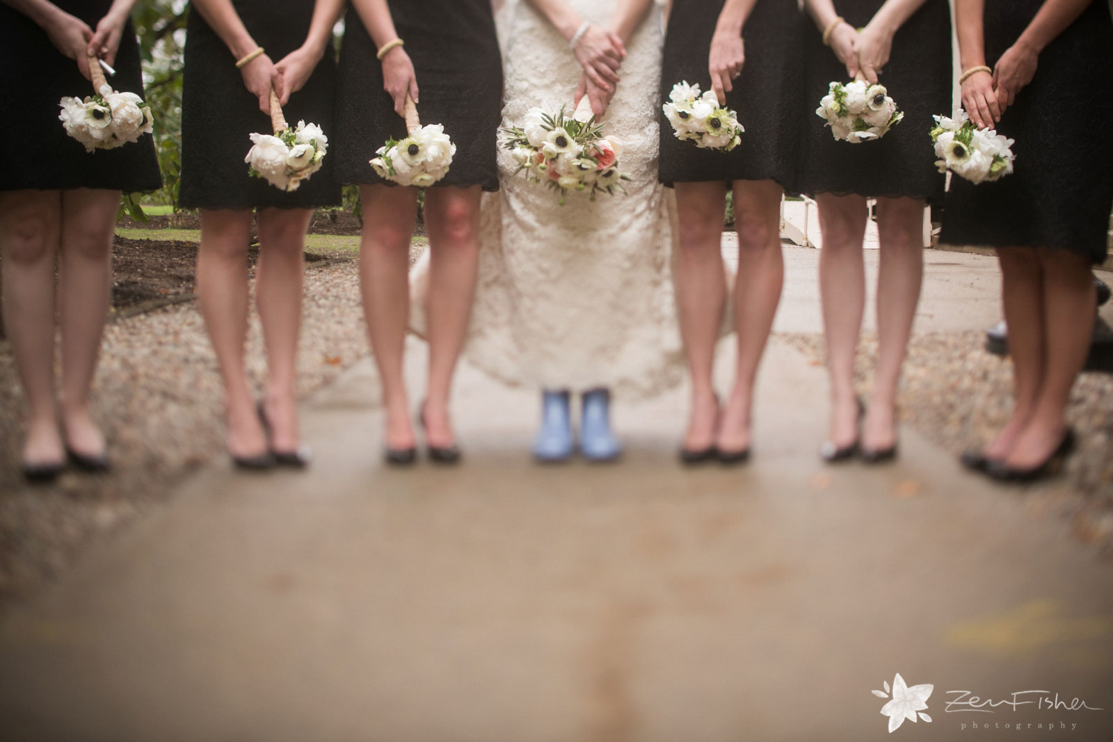Playful detail of bridesmaids standing in a row, holding bouquets and bride wearing blue galoshes.