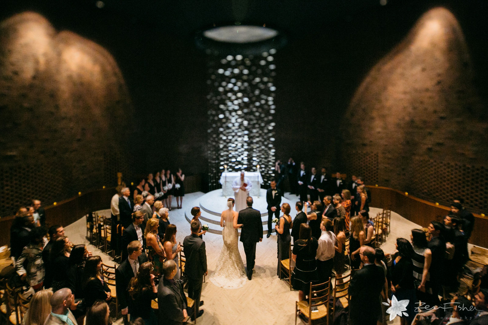 Bride walking down the aisle from behind, with bridal party circling altar, at magical MIT chapel.