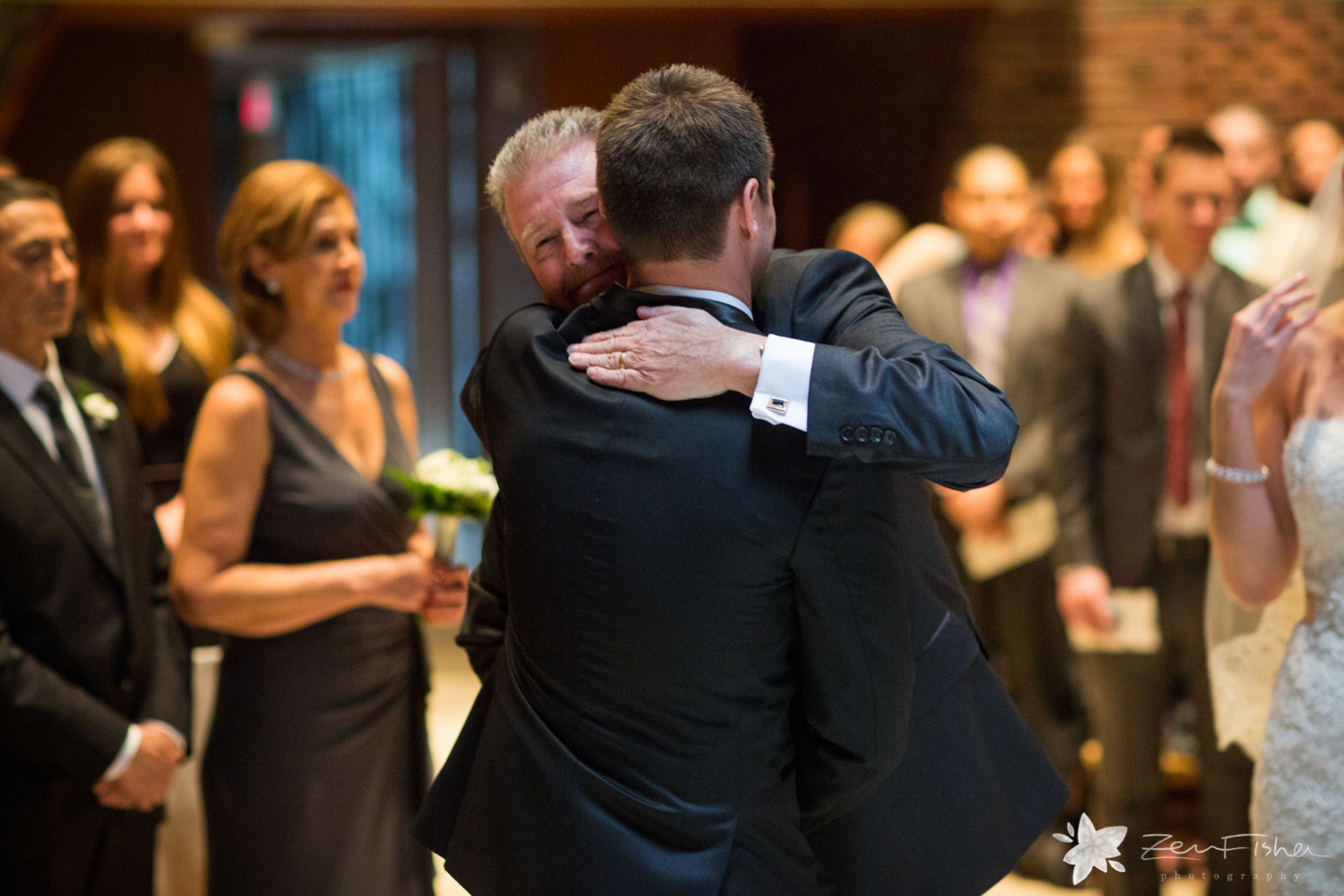 Father of the bride gives away his daughter and hugs the groom in an emotional embrace.