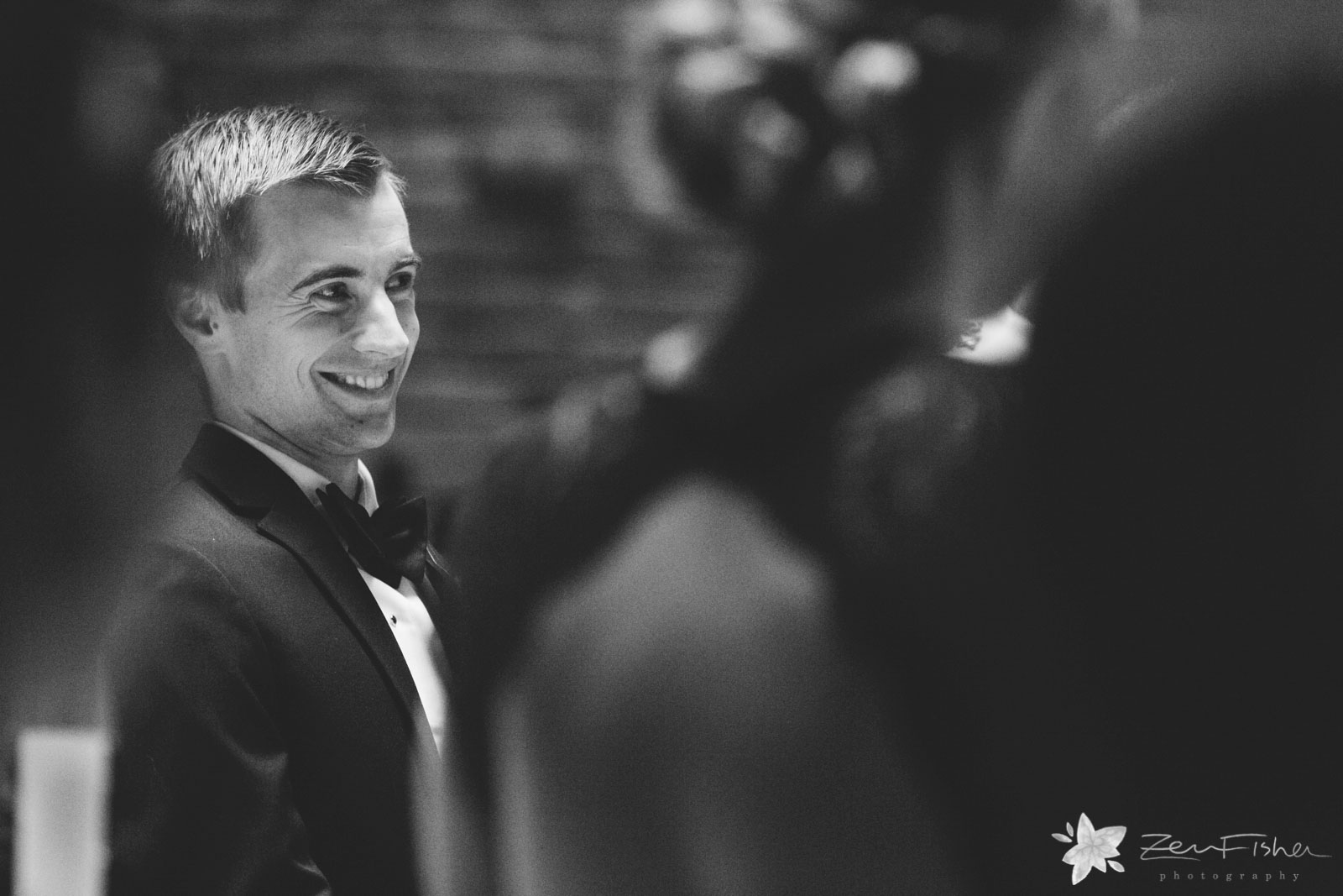 Peeking between people to see best man with a big happy smile during ceremony.