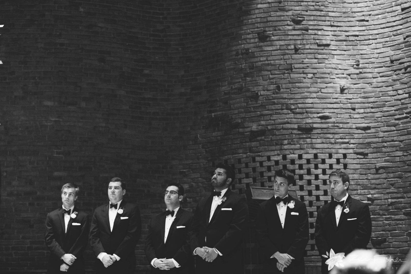 Groomsmen stand in a line in front of brick wall, intently watching ceremony unfold.