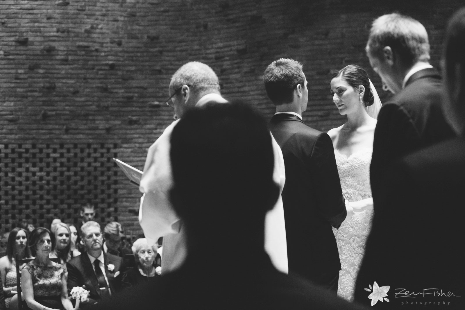 Dramatic black and white of bride looking away during ceremony with natural light falling from above