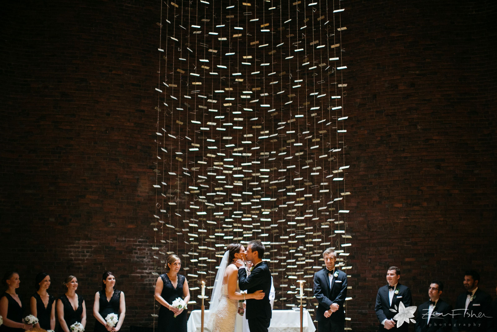 Bride and groom pull each other in lovingly and kiss at altar in front of large artistic sculture.