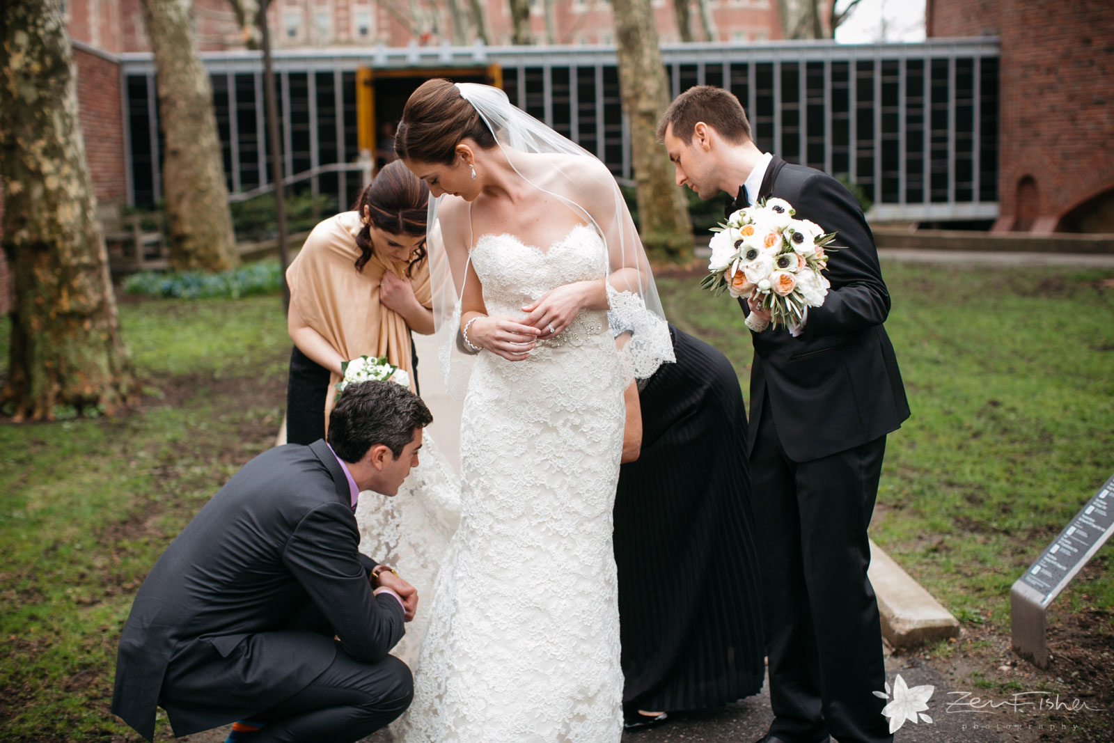 Candid of bridesmaids helping bustle bride's dress outside the church on the rain-soaked path.