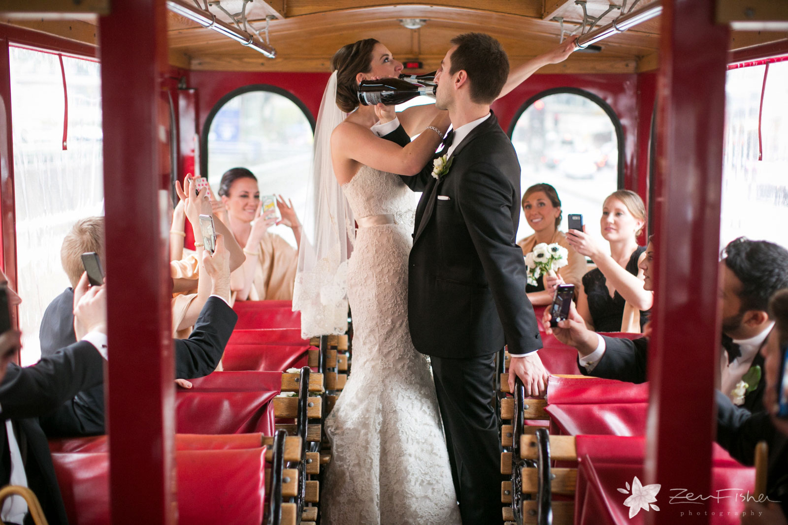 Silly bride and groom stand in the aisle of the party trolley and chug from champagne bottles.