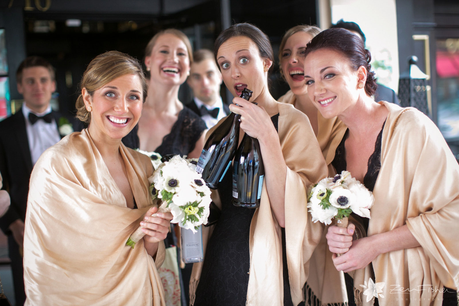 Bridesmaids being silly, making funny faces and holding champagne bottles.