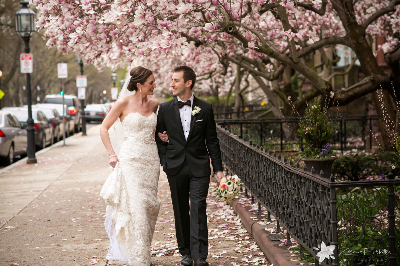 Bride and groom walking together under lush pink and white blossoming magnolia trees.