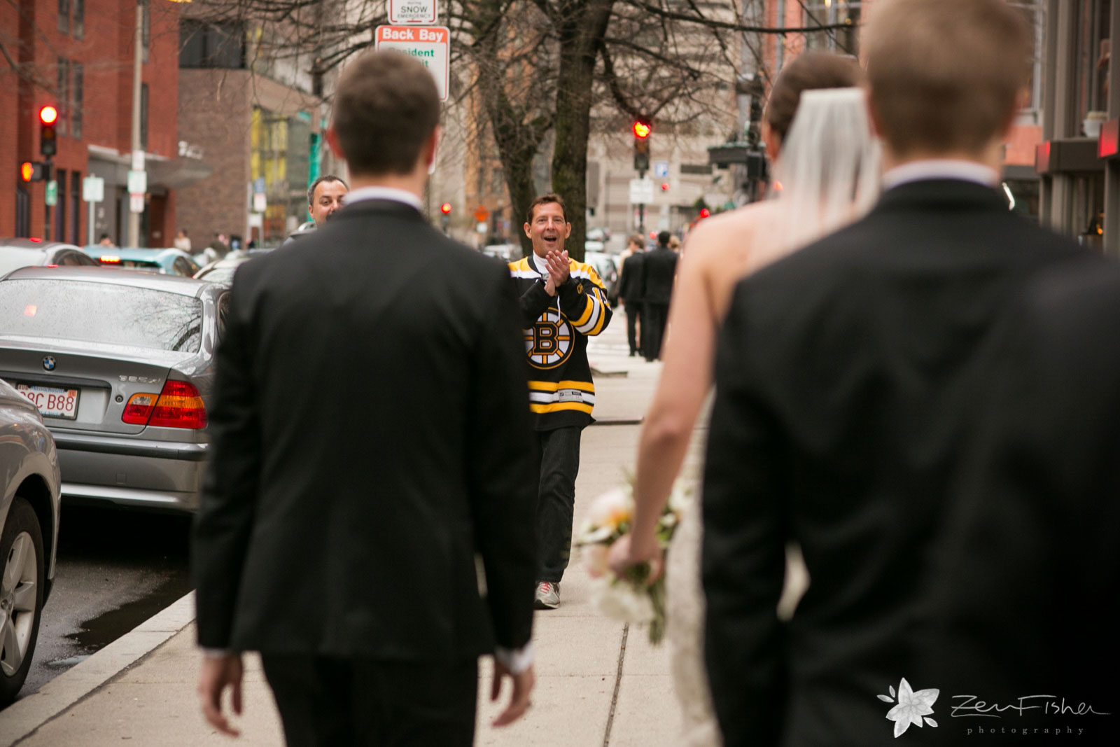 Passersby on the sidewalk smiling and clapping at the newly married couple.