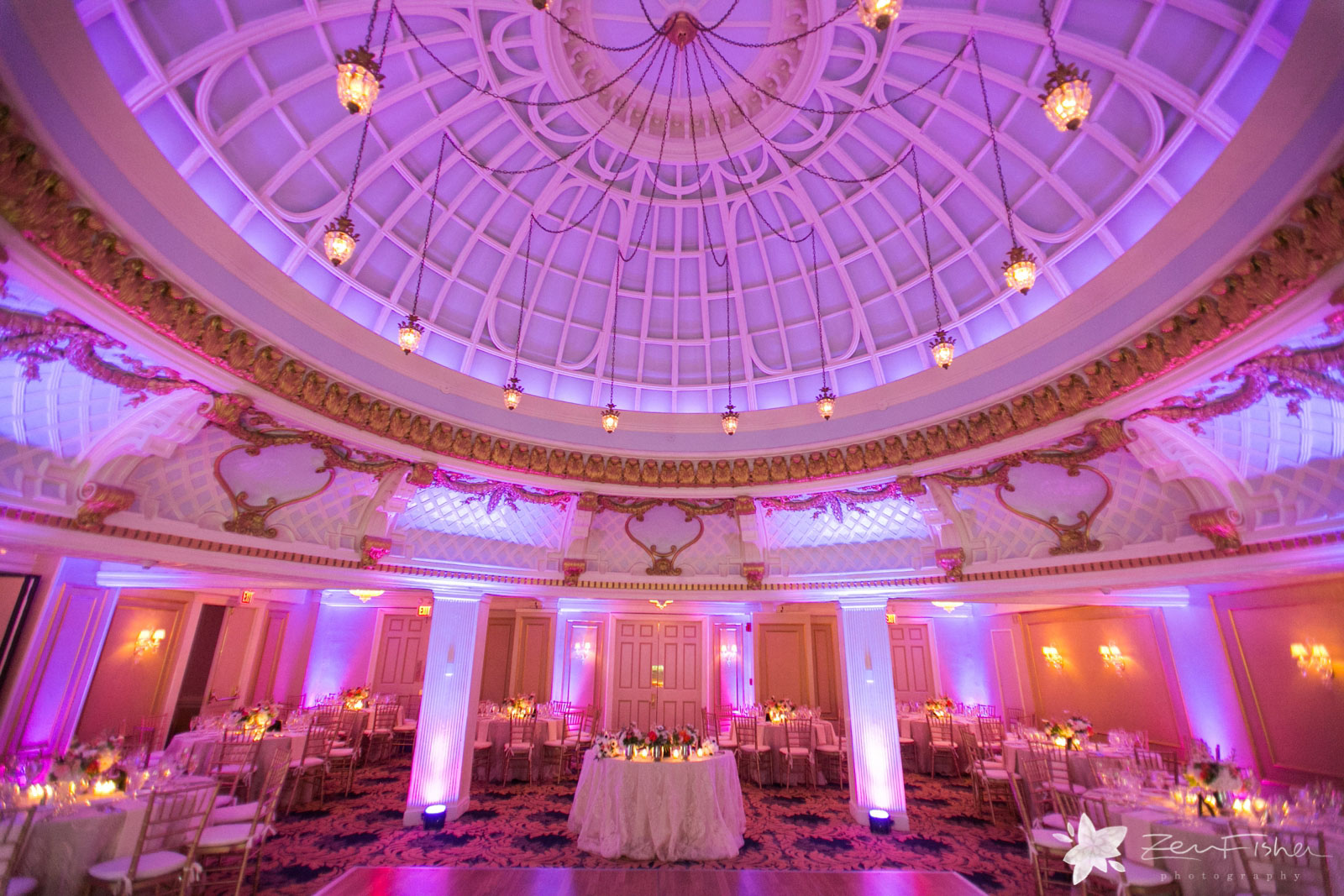 Wide shot of reception hall at Lenox with large dome, magenta lighting, and elegant architecture.