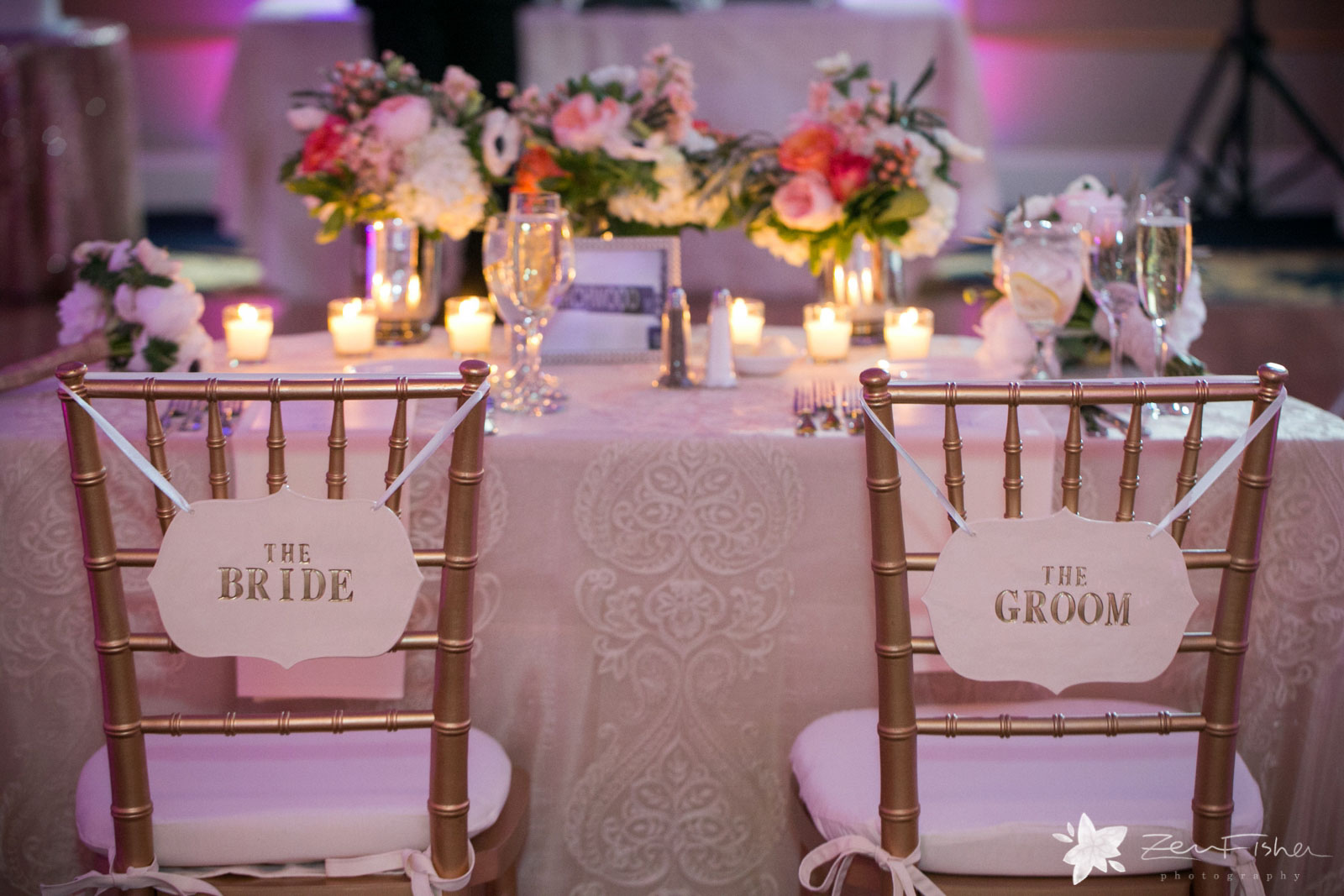 Details of the sweetheart table and the bride and groom's chairs with bouquets decorating the table.