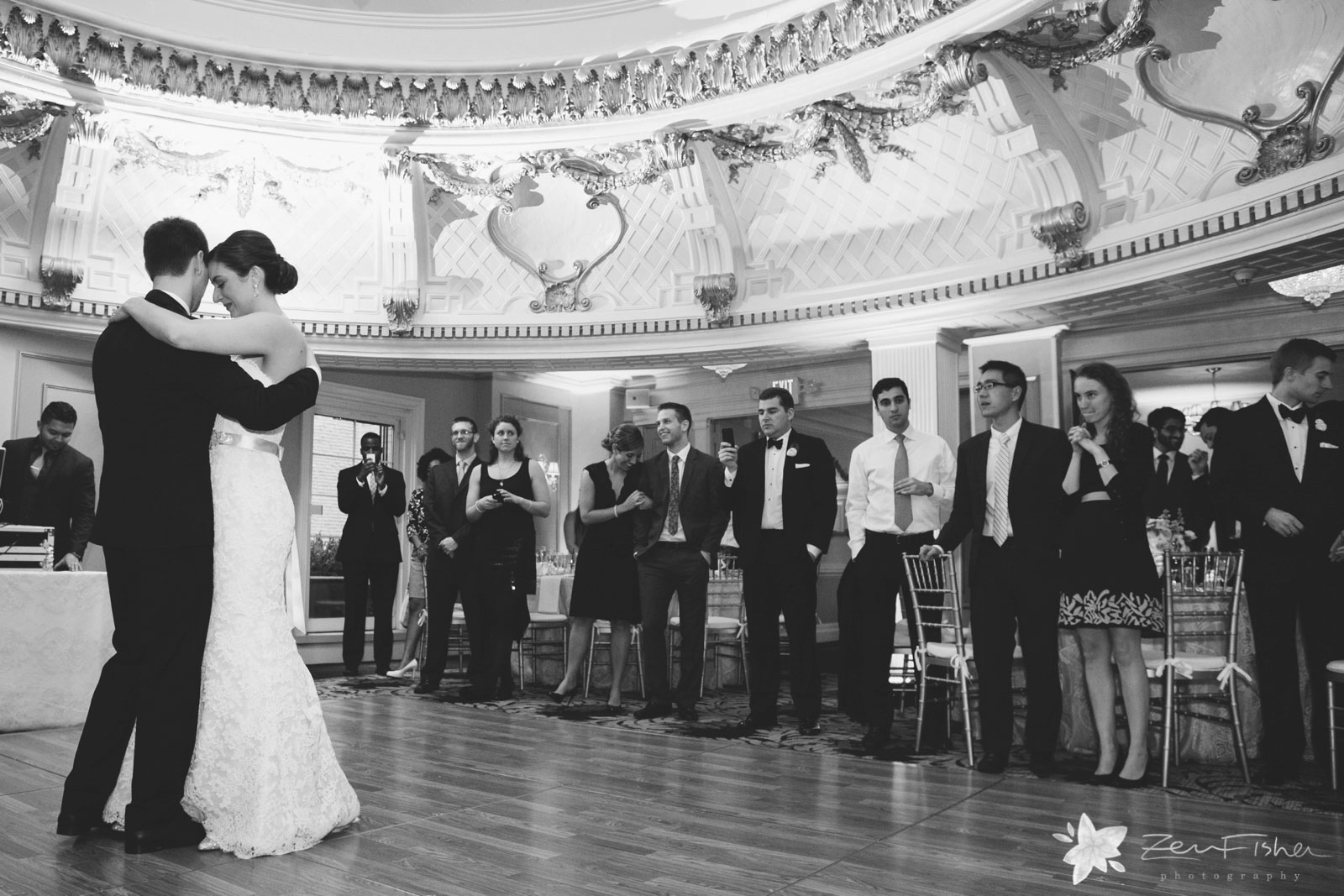 Bride and groom hold each other closely, share their first dance in the middle of the reception hall