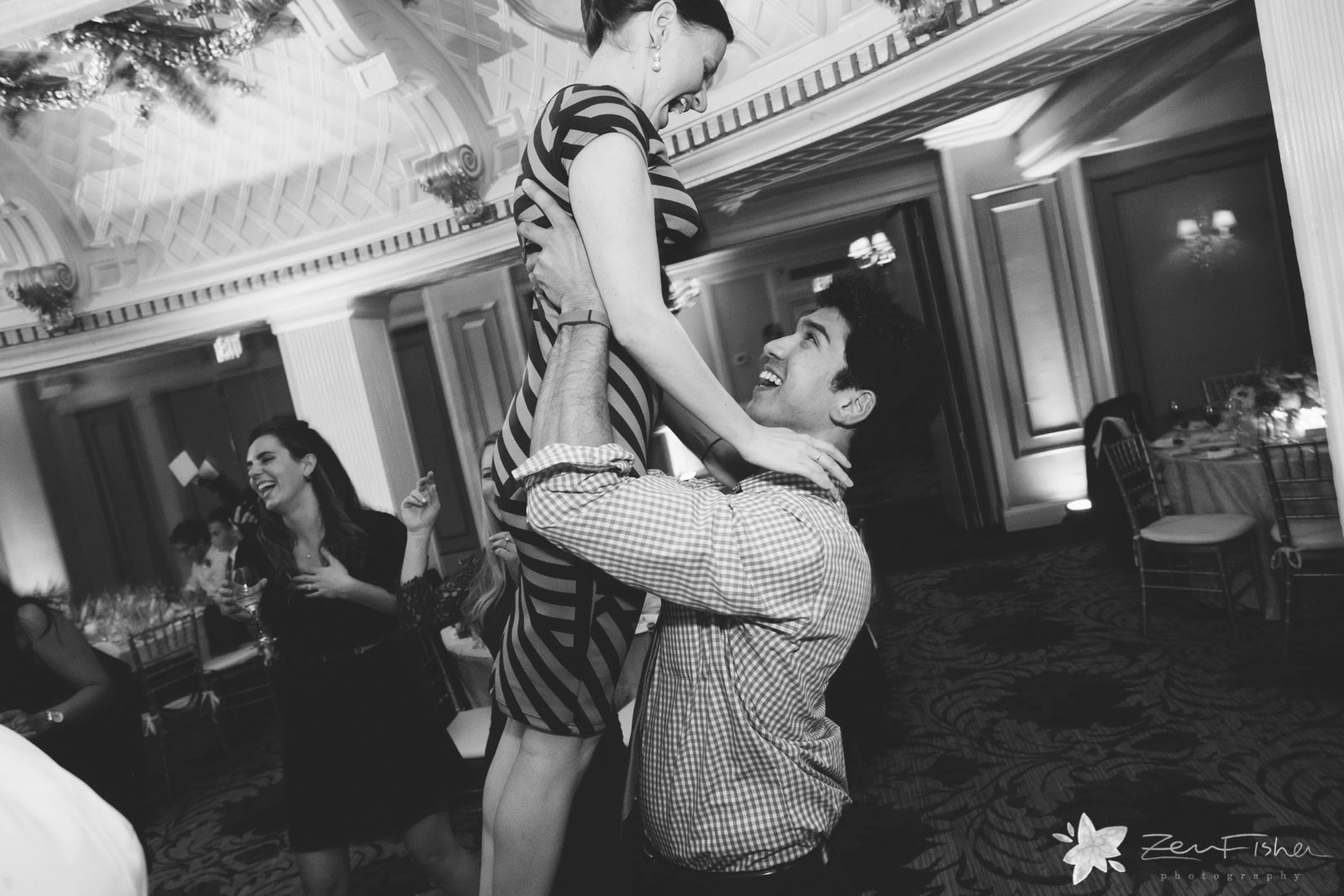 Guests being silly of the dance floor, man lifts woman in the air.