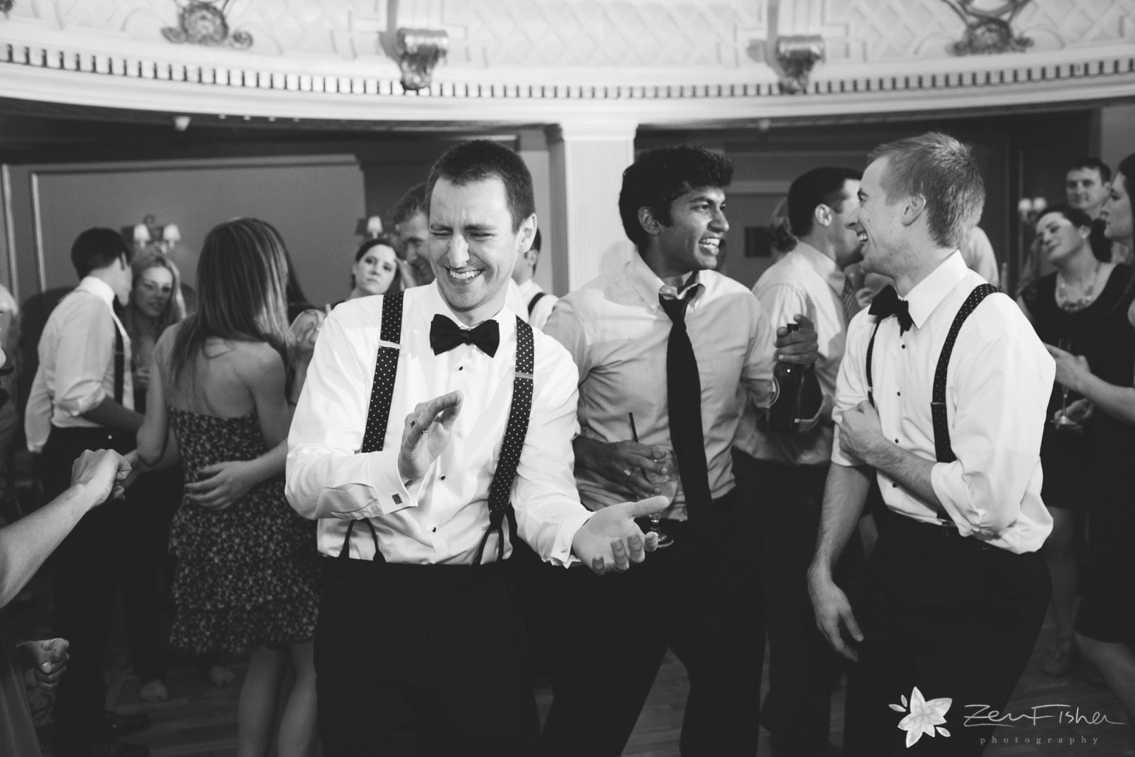 Groom having fun with his buddies and cracking up on the dance floor.