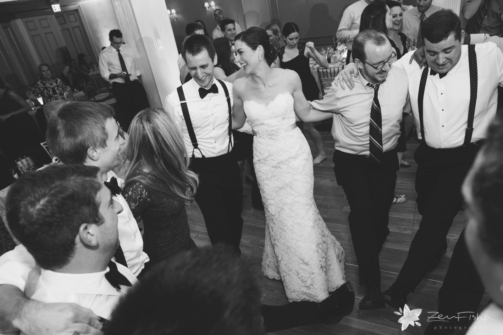 Bride, groom, and friends make a circle and dance together on the dance floor.
