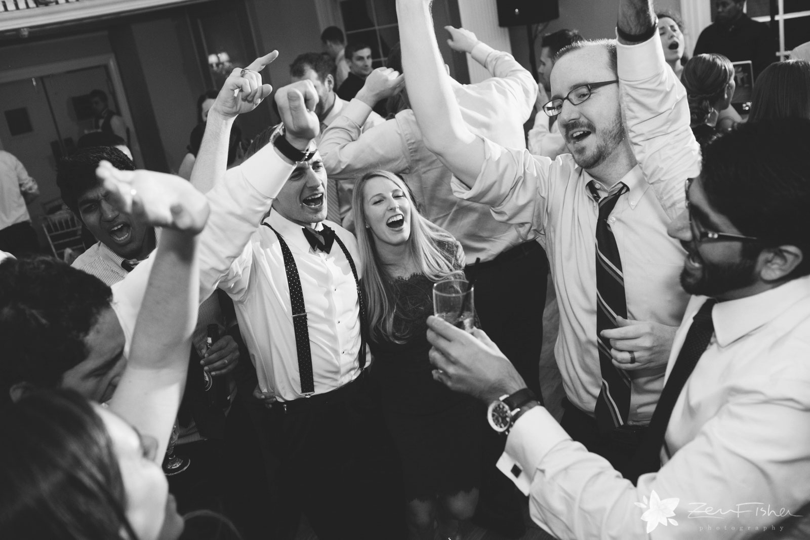 Guests shout and throw their hands up on the dance floor.