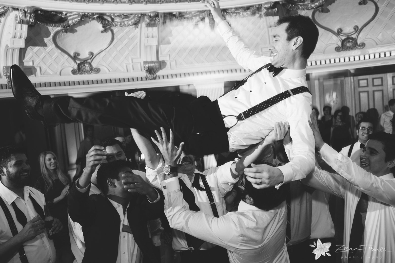 Epic shot of the groom crowdsurfing on the dance floor, in black and white.