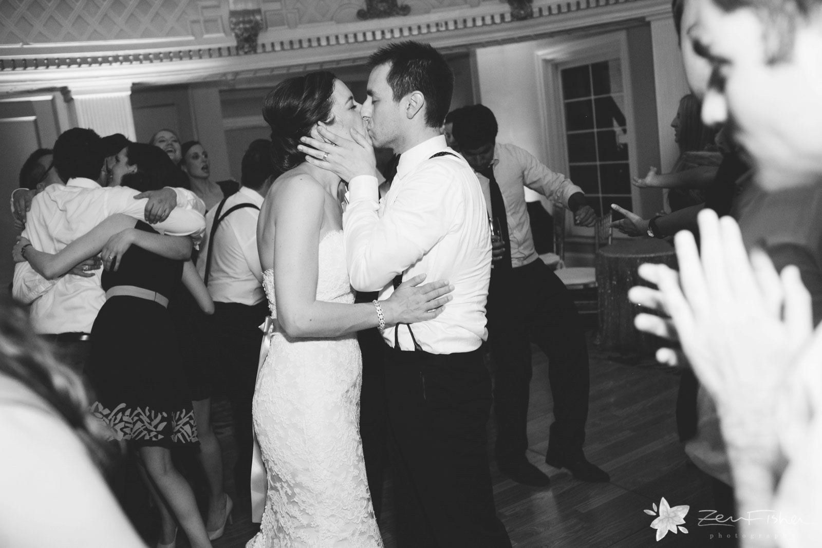 Bride and groom hold each other close and kissing on the dance floor, in black and white.