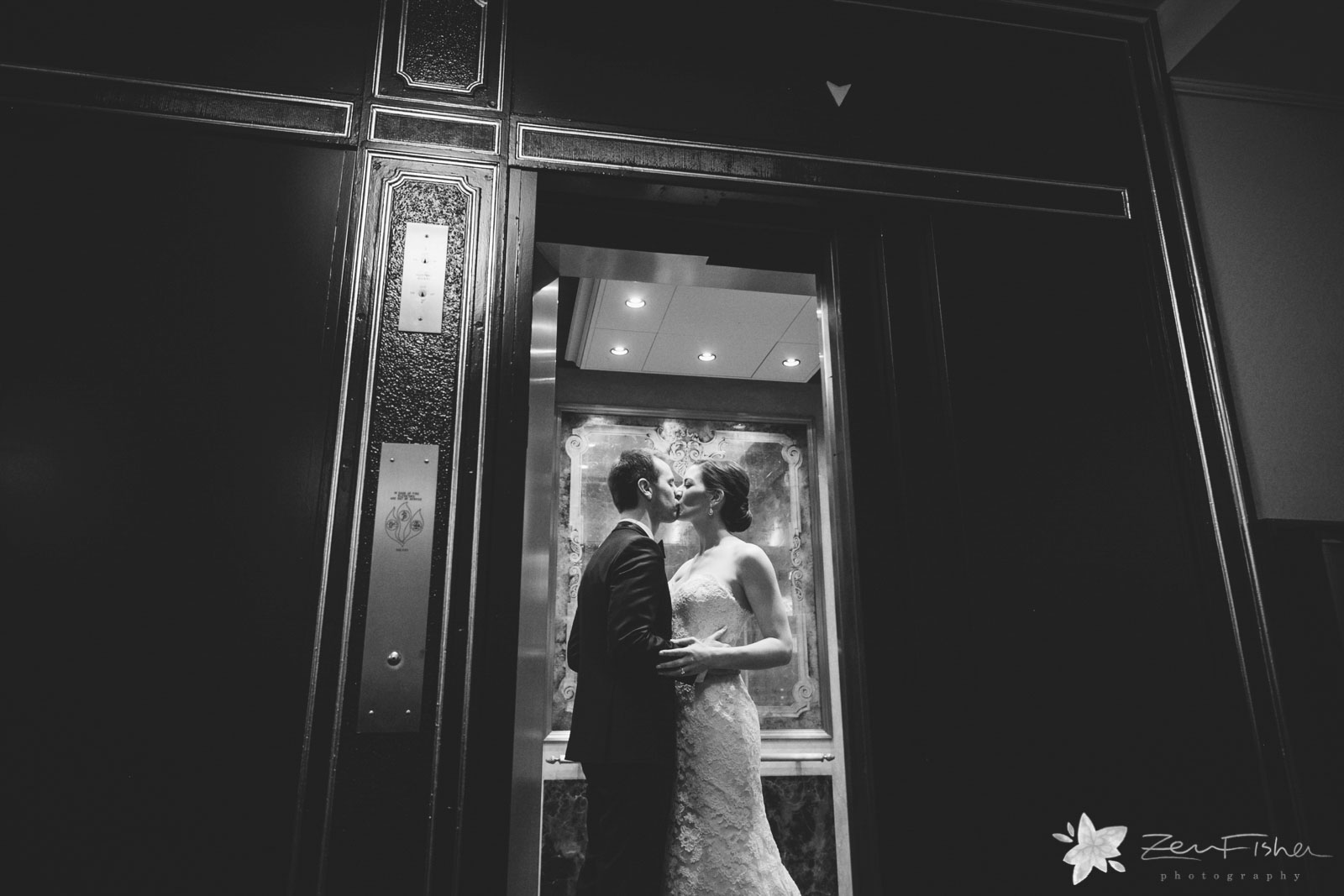 Bride and groom hold each other and kiss in elevator as doors close, epic lighting.