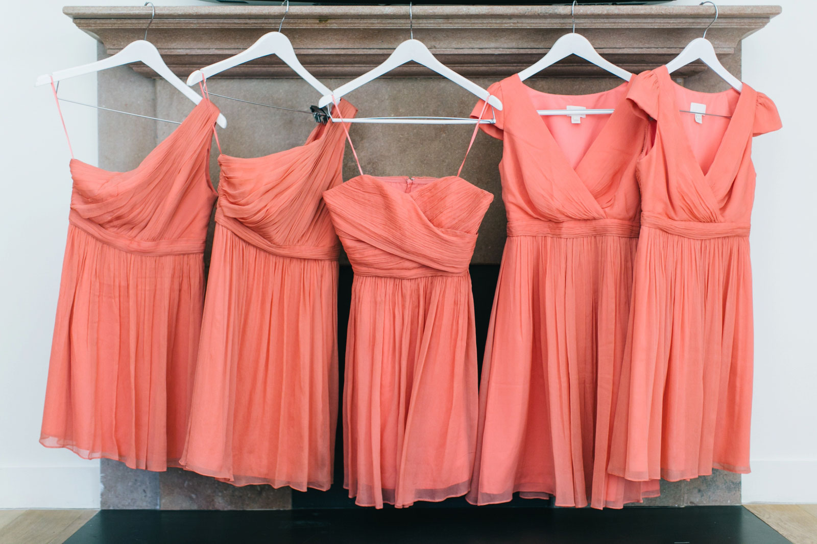 mismatched short salmon pink bridesmaids dresses hanging up in bridal suite at Ames Hotel
