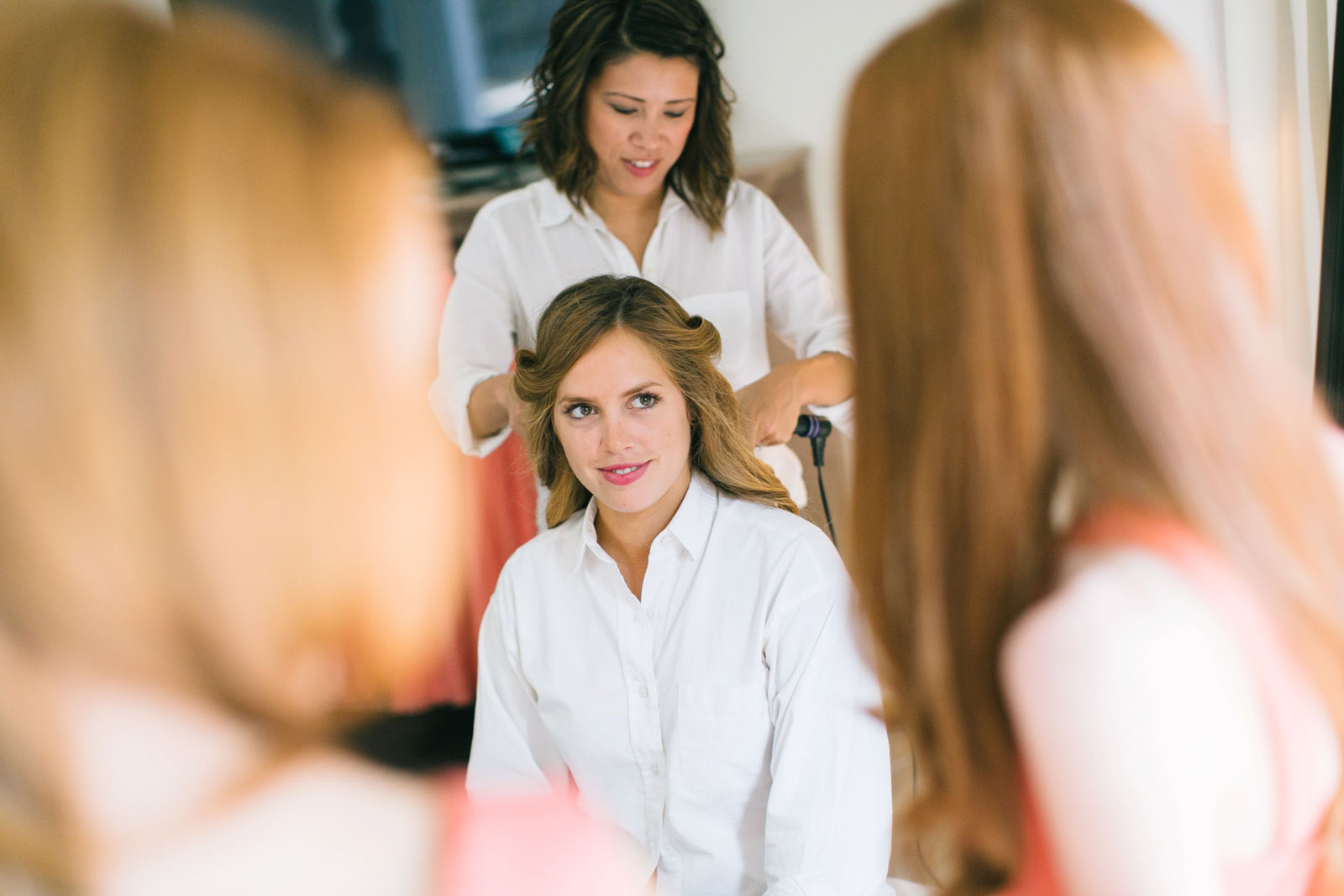 bridesmaid getting her hair done while getting ready in bridal suite with lots of natural light
