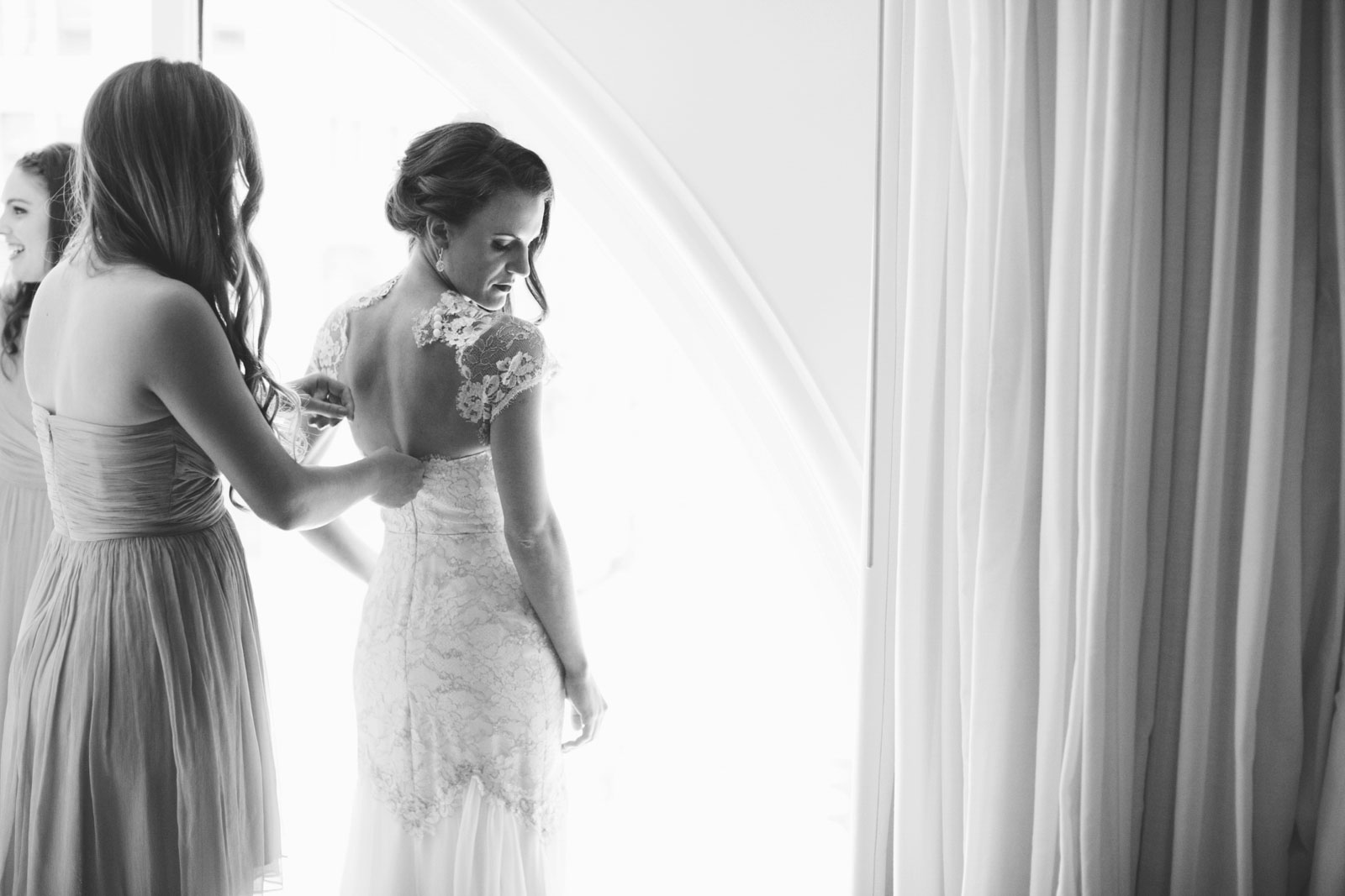 black and white shot of bridesmaid helping bride into backless lace dress in front of window