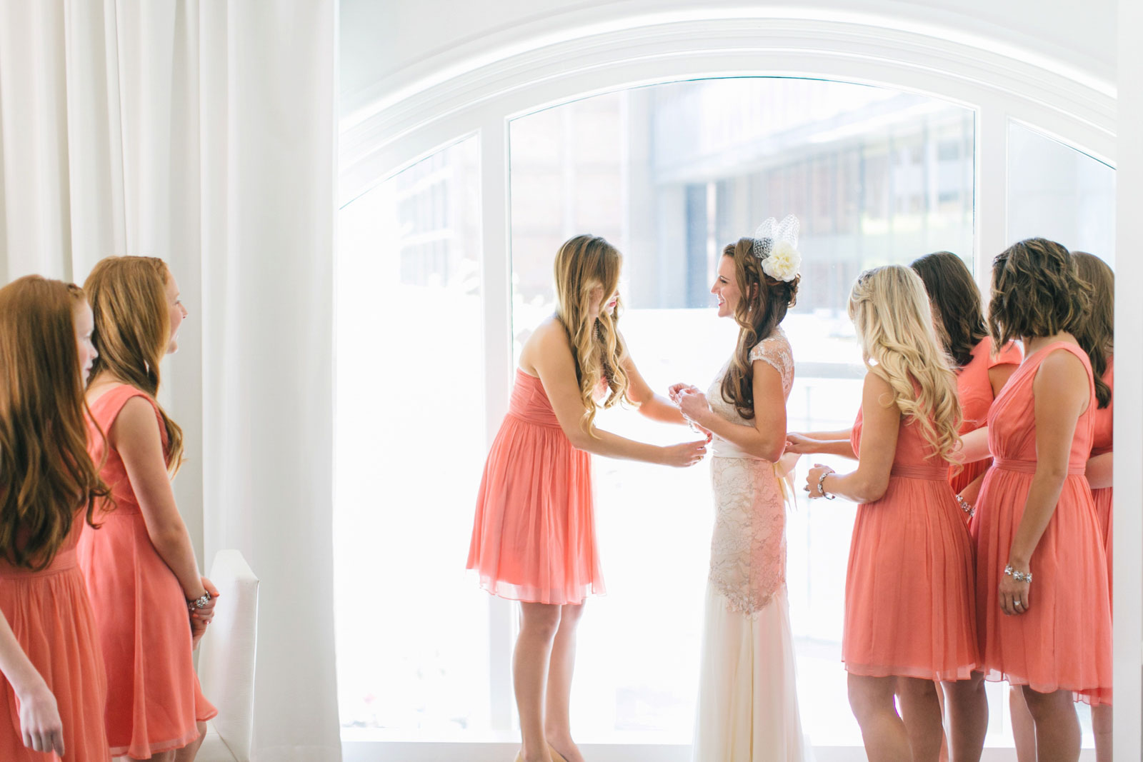 bridesmaids helping bride into her wedding dress in front of large window in bridal suite at Ames