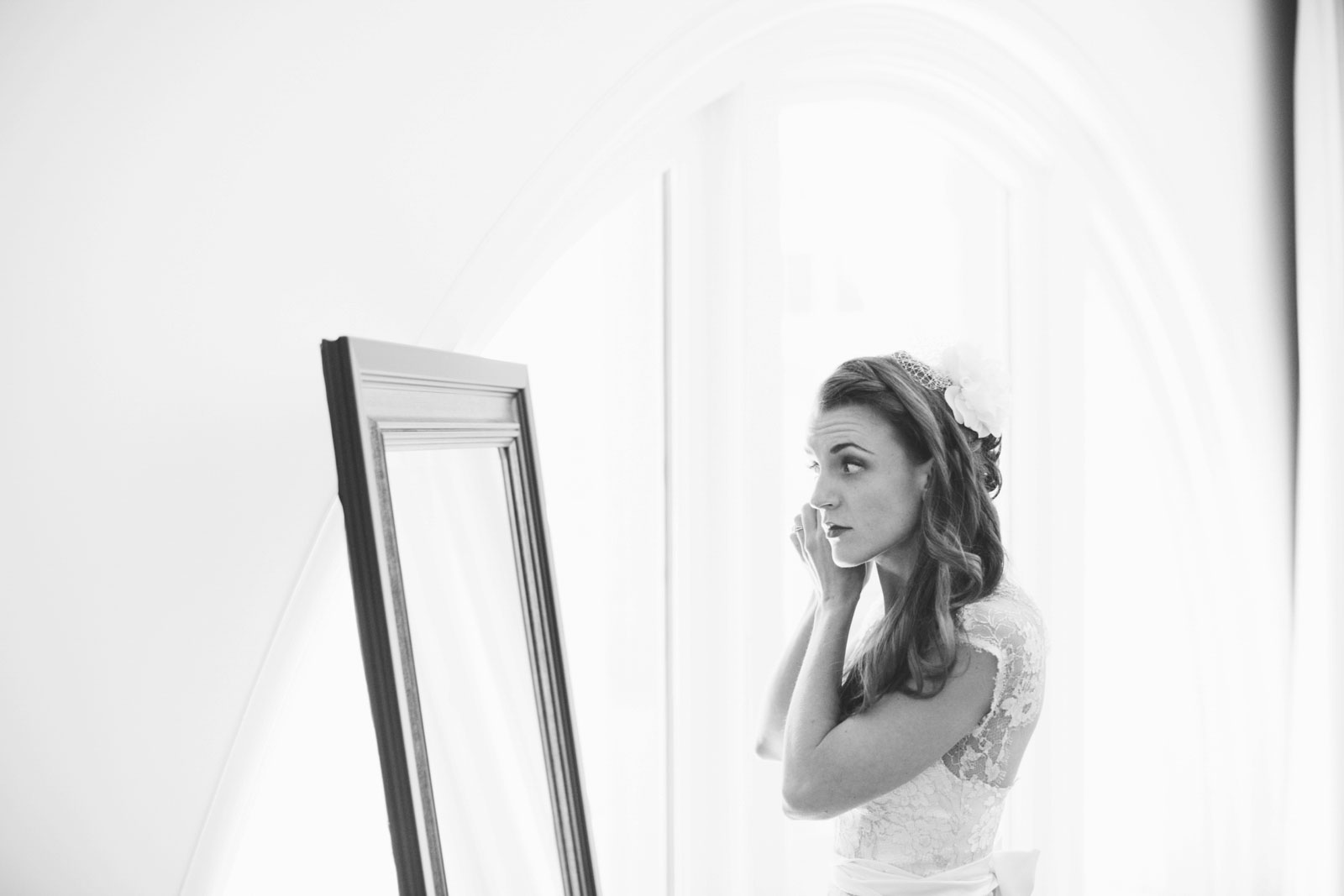 black and white shot of bride looking in mirror and putting earrings on while getting ready