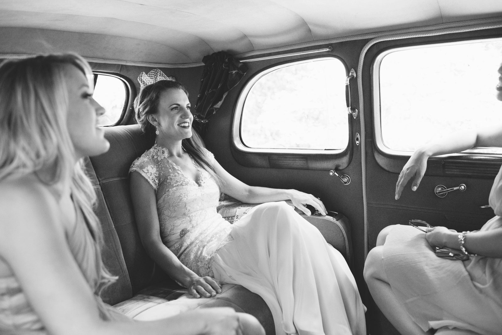 black and white candid of bride catching a ride in vintage car on the way to wedding ceremony