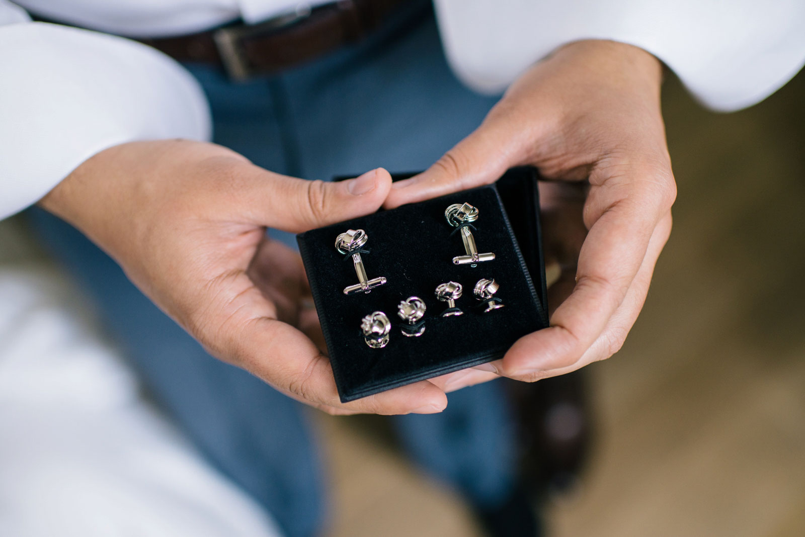close up shot of groom holding box with silver knot cufflinks with matching buttons