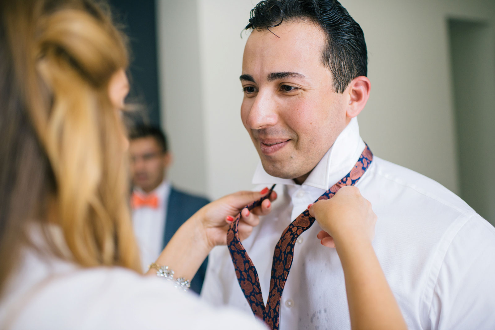 groom's friend helping groom put on vintage paisley bow tie while getting ready