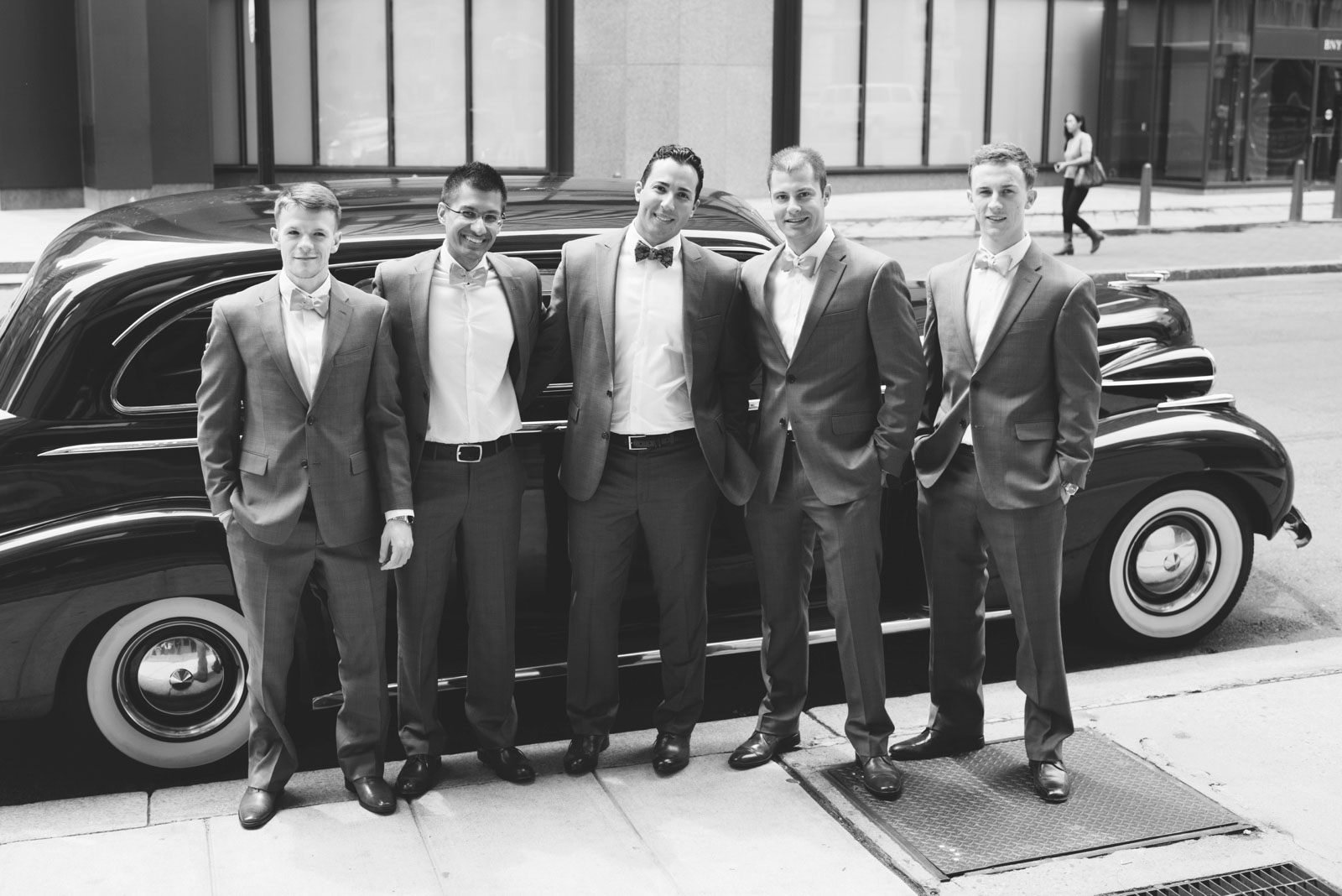 black and white shot of groomsmen standing outside of vintage car on the way to wedding ceremony