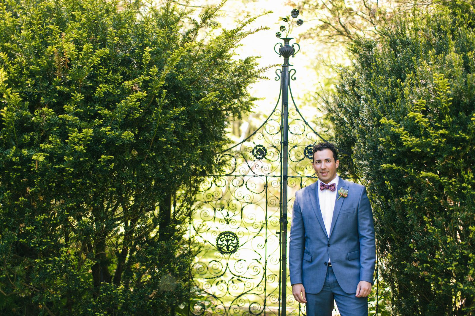portrait of groom in front of antique wrought iron gate at Mass Audubon's wildlife sanctuary