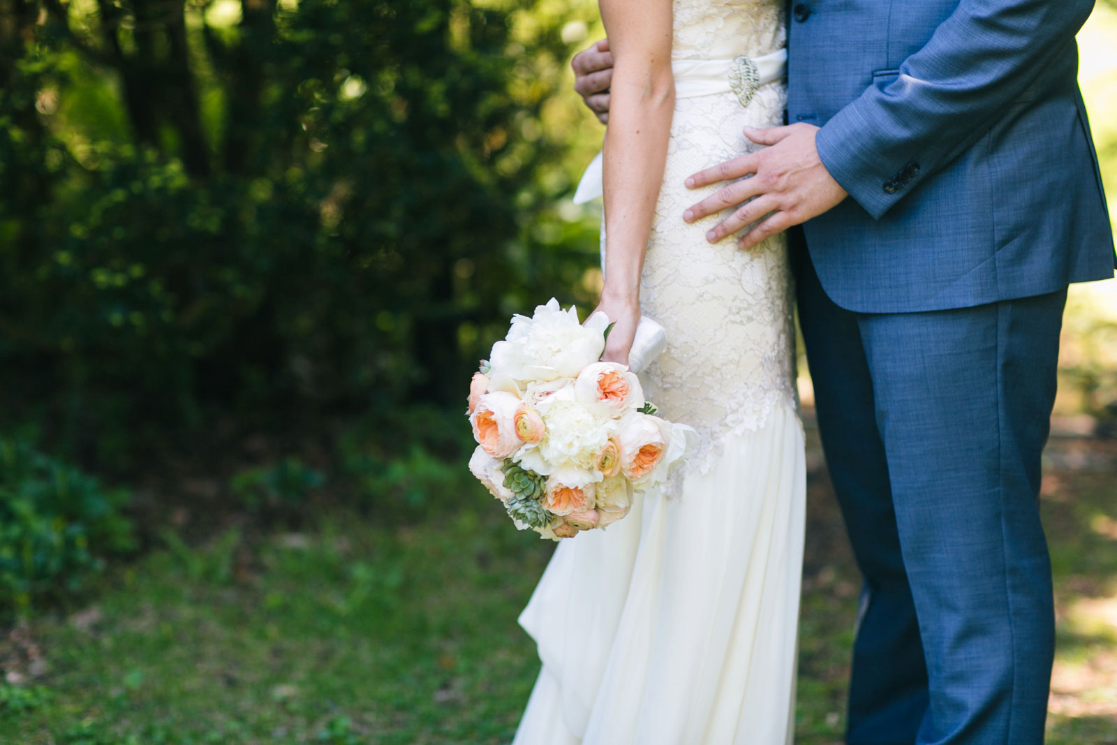 groom holding bride close during their first look, bride holding bouquet with light peach peonies
