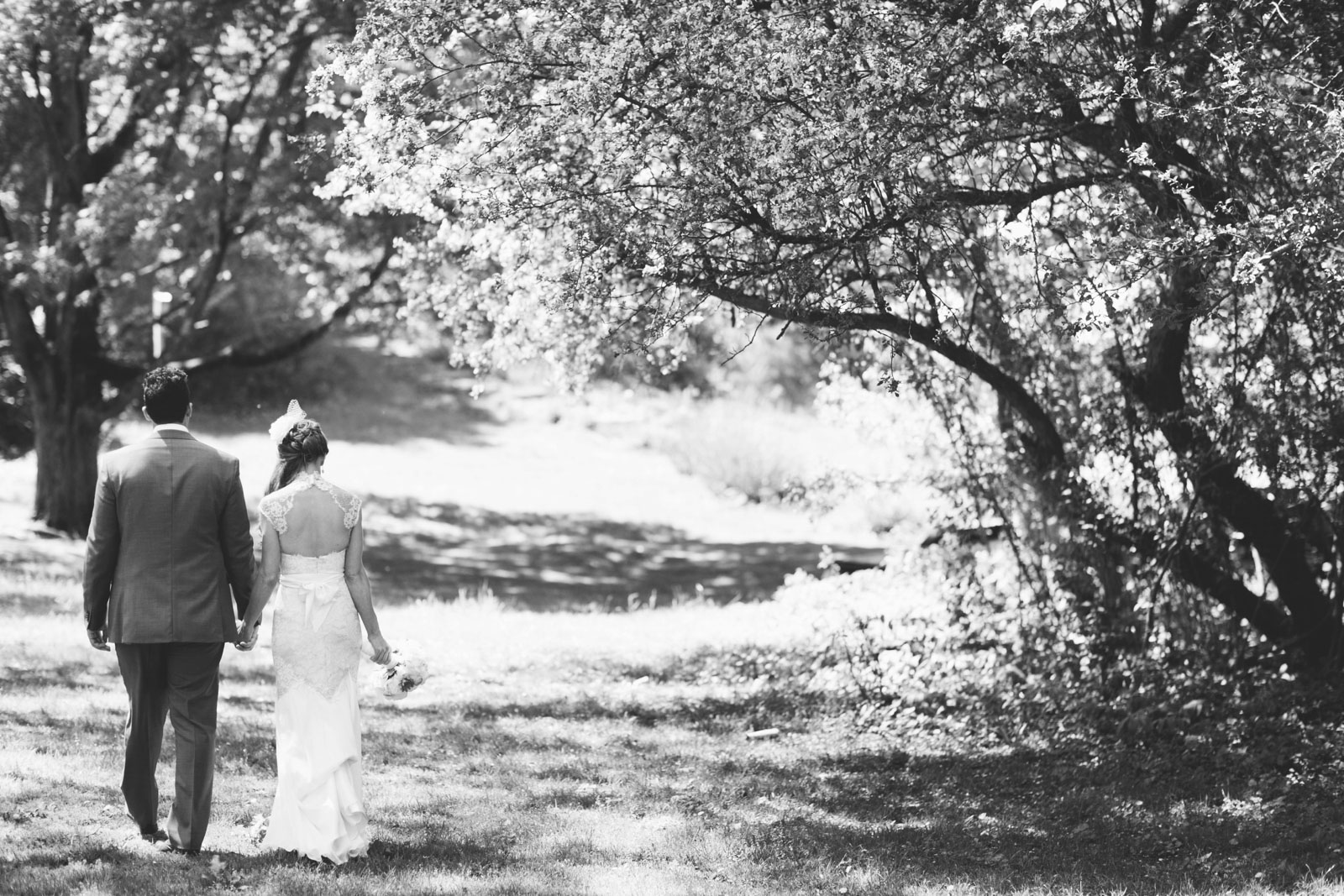 black and white portrait of bride and groom walking through wildlife sanctuary at Mass Aububon