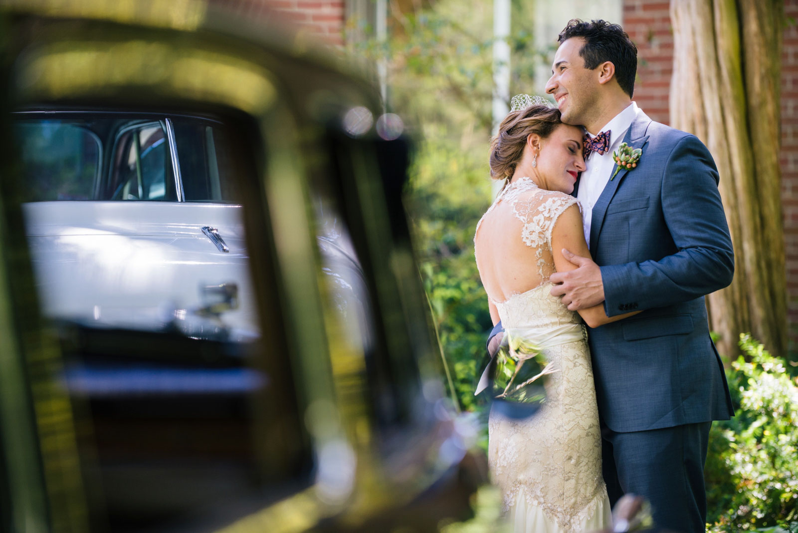 intimate portrait of couple next to old-school car at vintage-inspired wedding at Mass Audubon