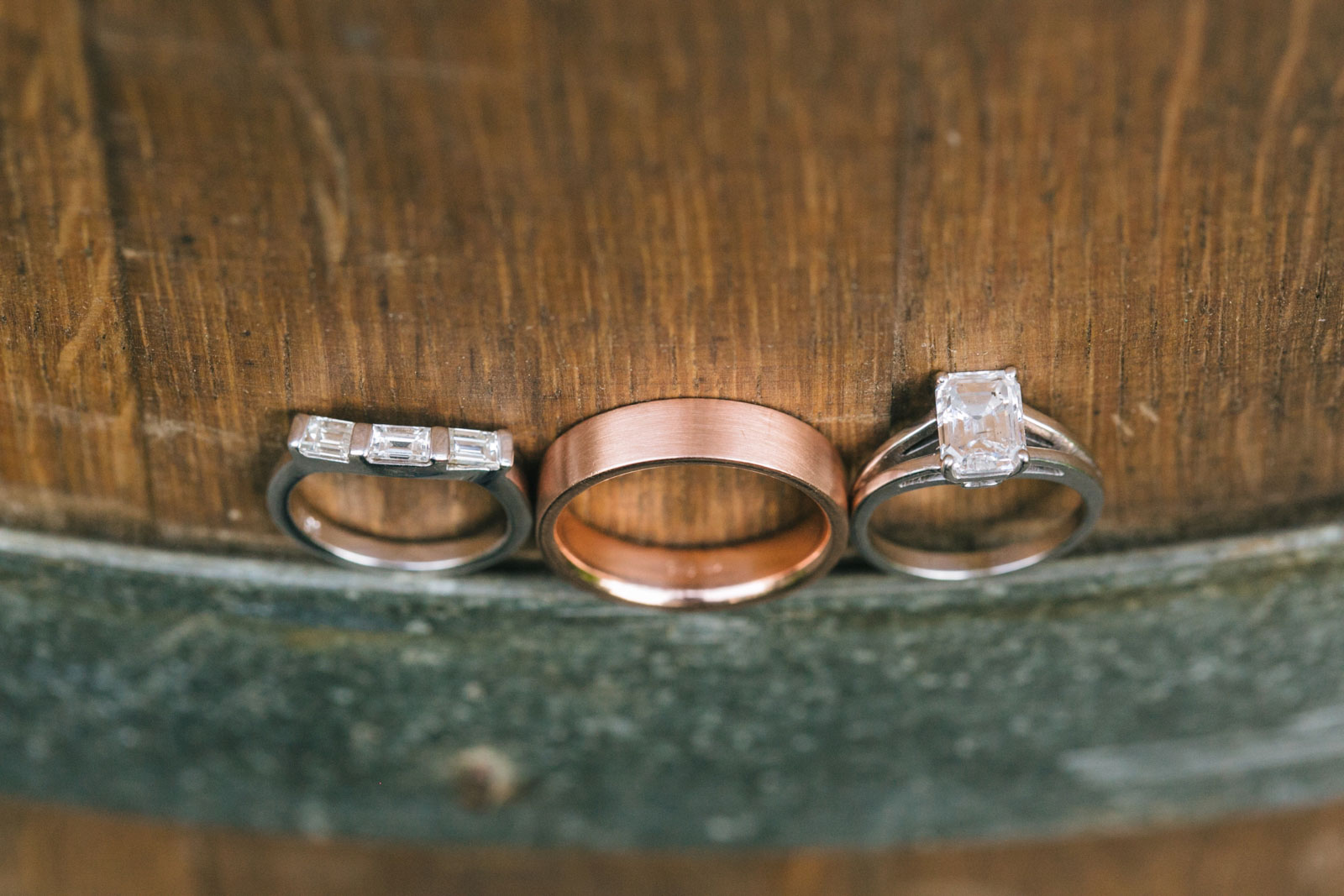 close up shot of simple wedding rings resting on antique wooden barrel at vintage-inspired wedding