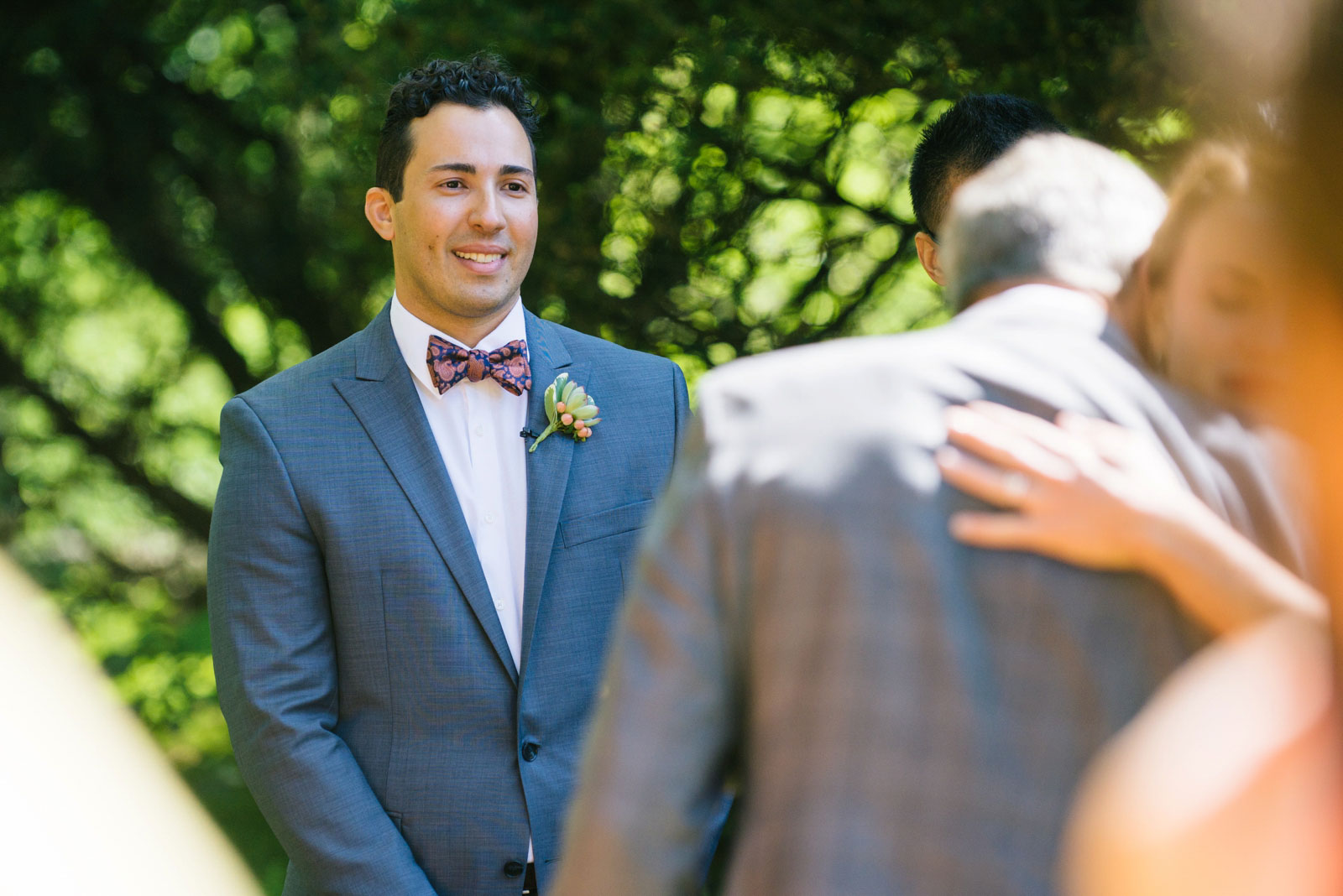 groom about to cry during wedding ceremony as father of the bride gives bride away