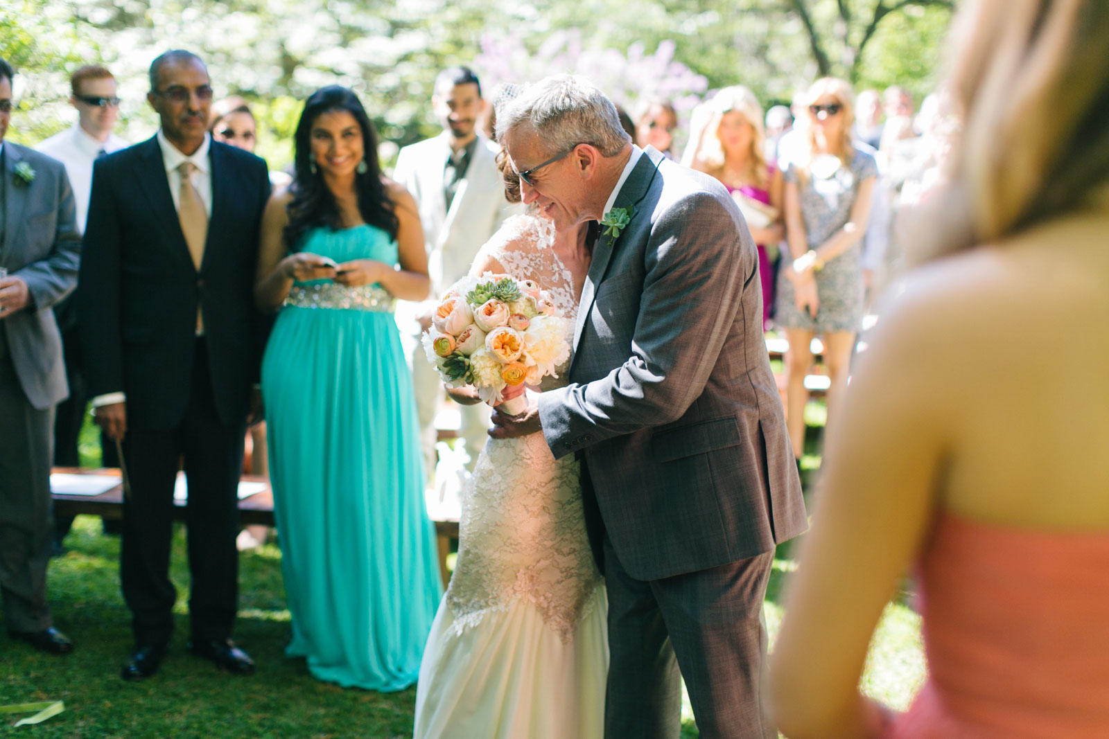 father of the bride giving bride away at sunny outdoor wedding ceremony in garden in Boston
