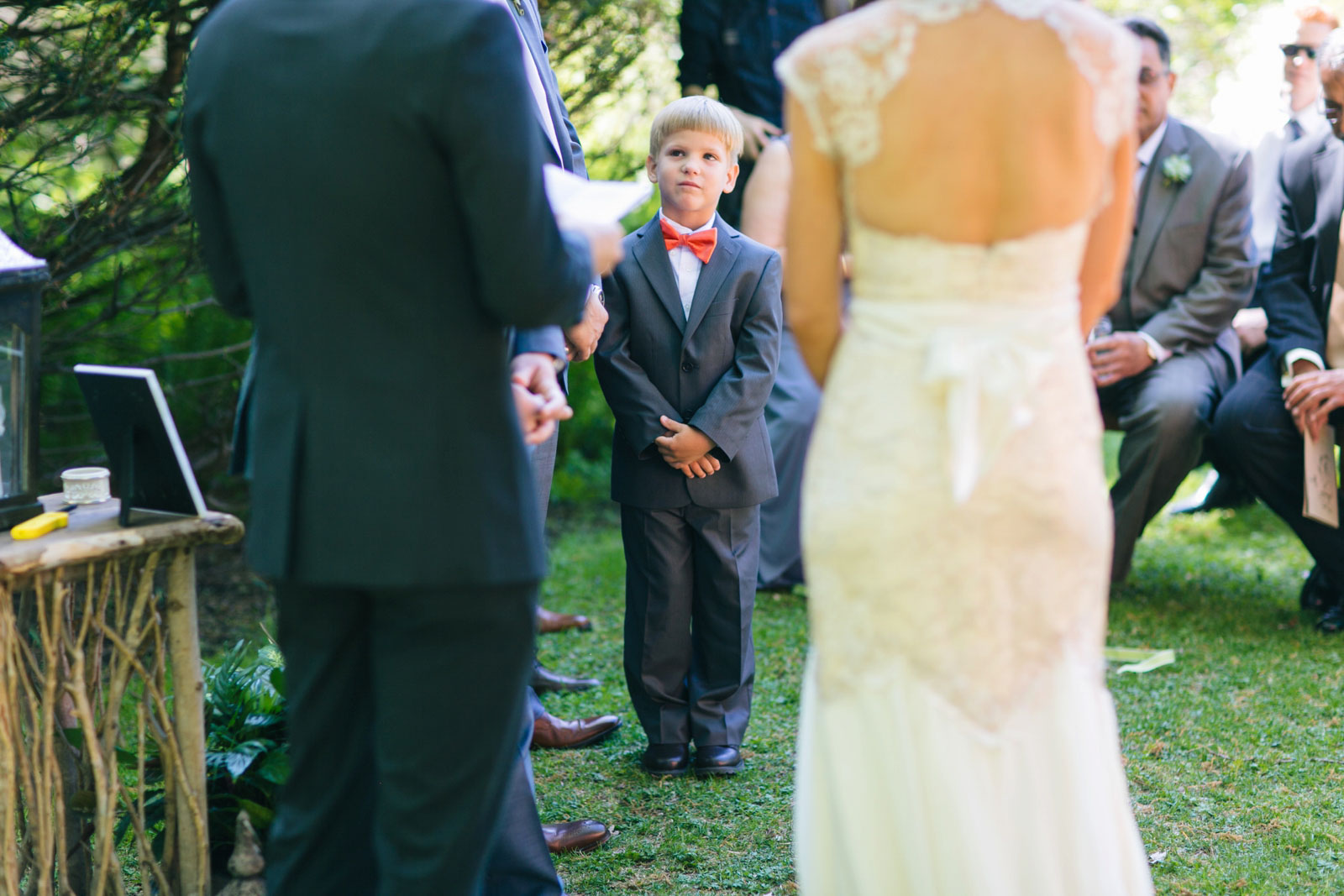 Ring bearer in suit and pink bow tie looks up at groom during wedding ceremony