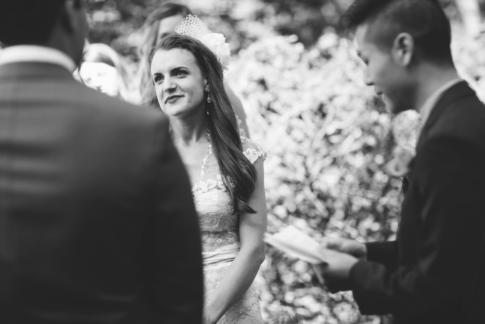 moody black and white shot of bride looking lovingly at groom while he says his vows