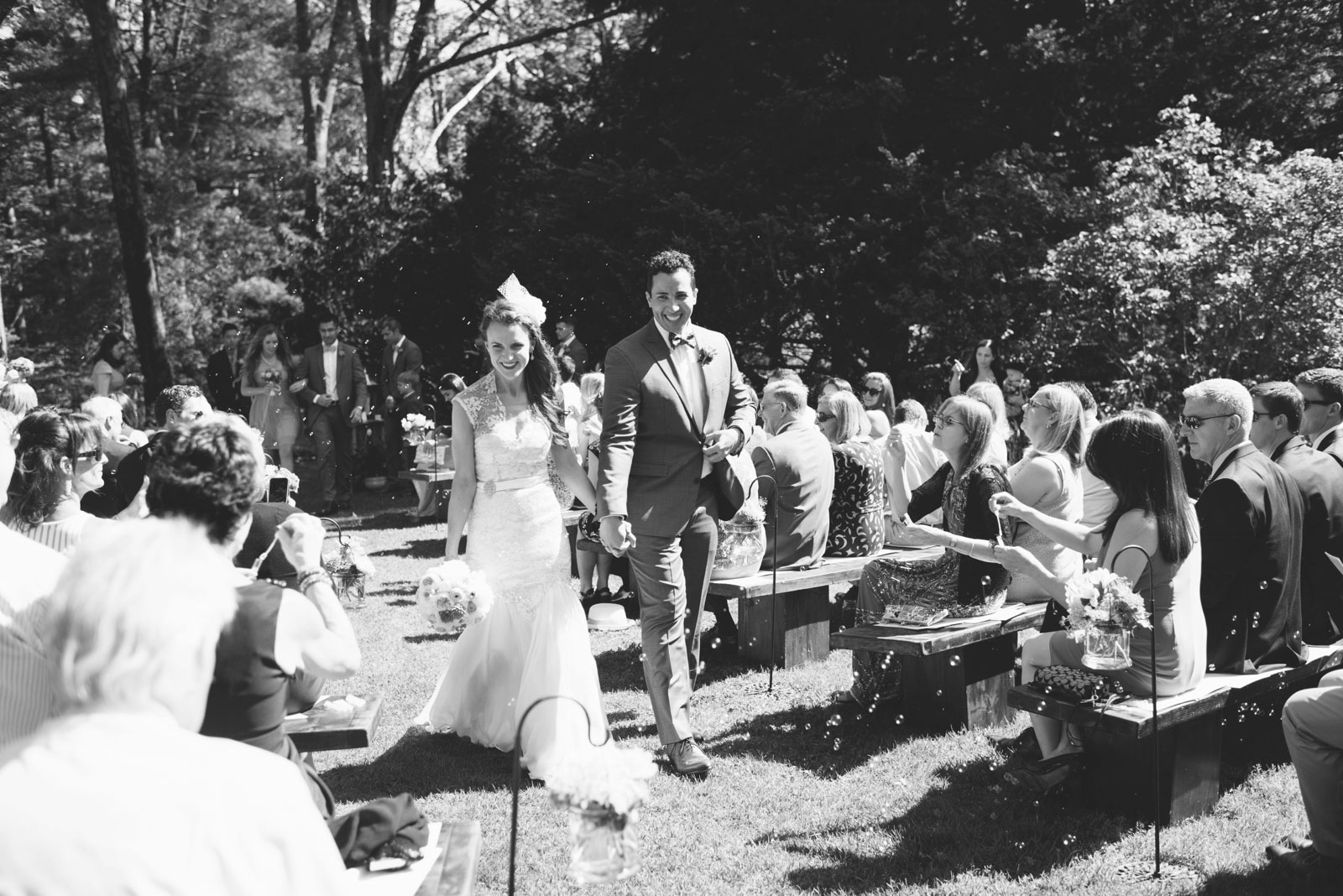 black and white shot of bride and groom walking back down the aisle together during bubble exit