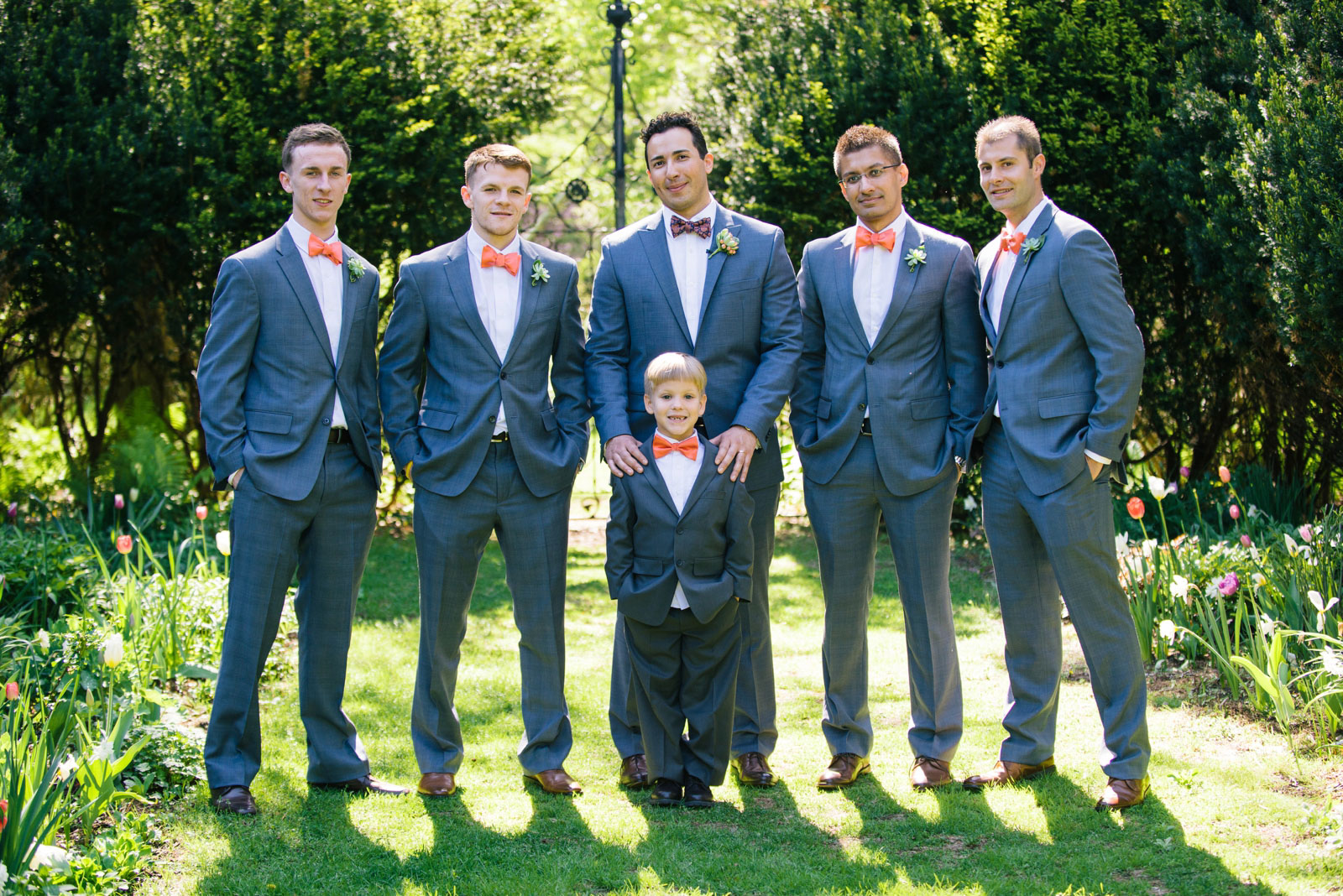 portrait of groomsmen with grey suits, salmon pink bowties, and succulent boutonnières