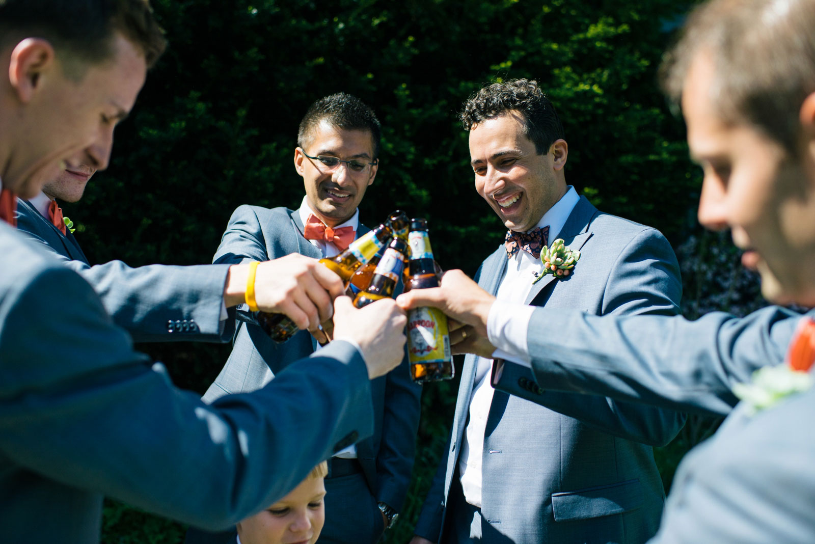candid shot of groomsmen sharing a toast drinking Harpoon beer and hanging out during portraits