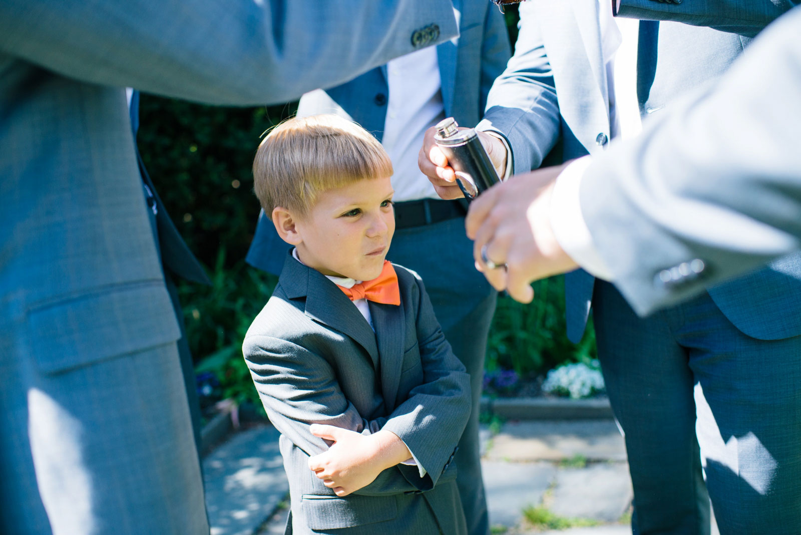 groomsmen offering drink to ring bearer during portrait session at outdoor wedding in Boston