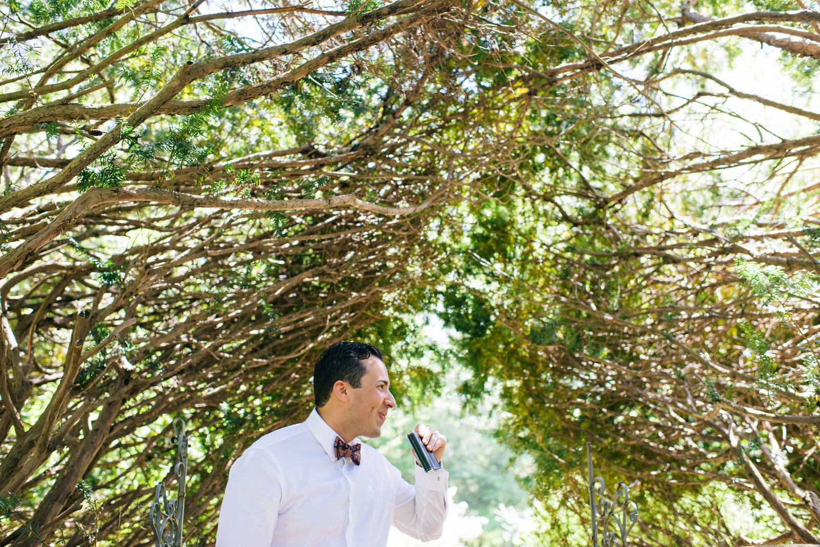 candid of groom drinking from his flask after Mass Audubon Wildlife Sanctuary wedding ceremony